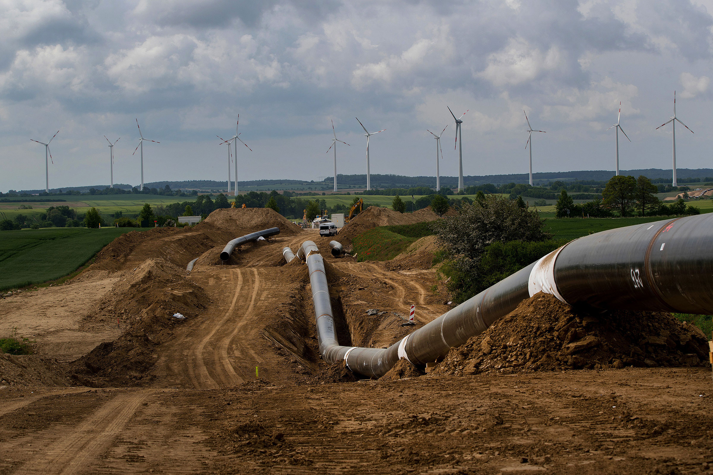 Sections of connected pipeline sit on the European Gas Pipeline Link site, as wind turbines operate in the distance in Gellmersdorf, Germany, May 28, 2019.