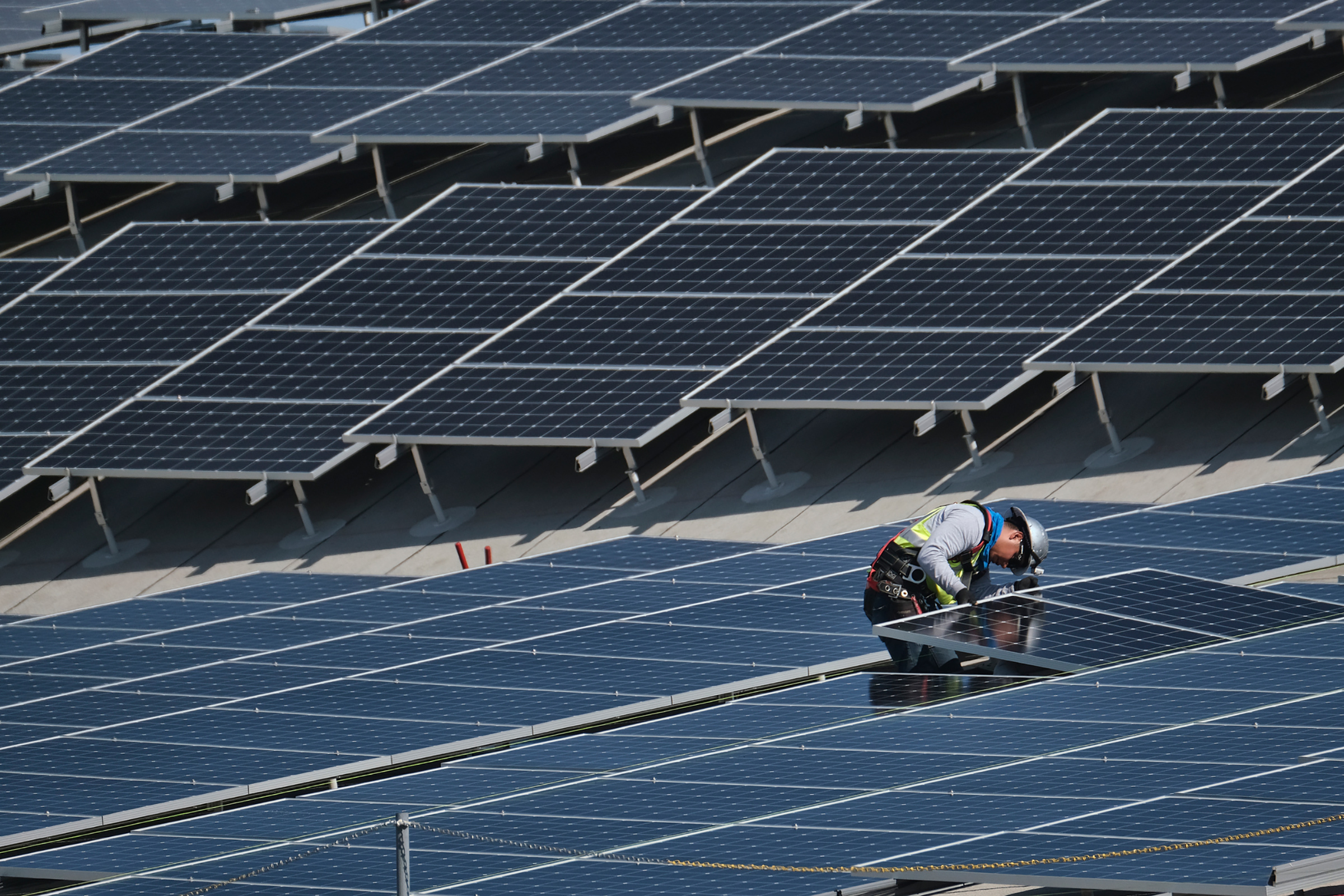 In this Aug. 8, 2019 photo a worker helps to install solar panels onto a roof at the Van Nuys Airport in the Van Nuys section of Los Angeles.
