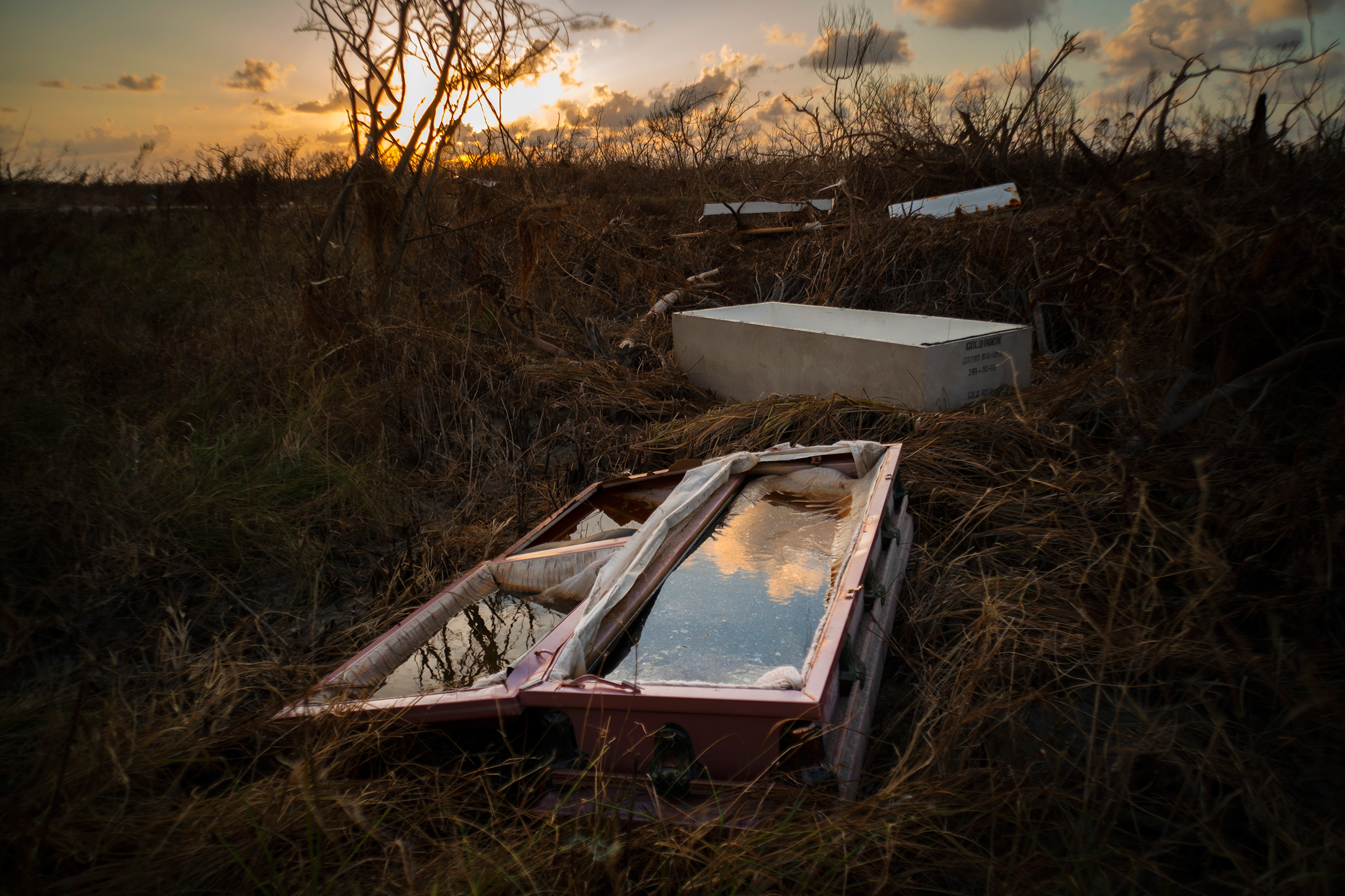 A water-filled coffin lays exposed to the elements in the aftermath of Hurricane Dorian, at the cemetery in Mclean's Town, Grand Bahama, Bahamas, Wednesday Sept. 11, 2019.