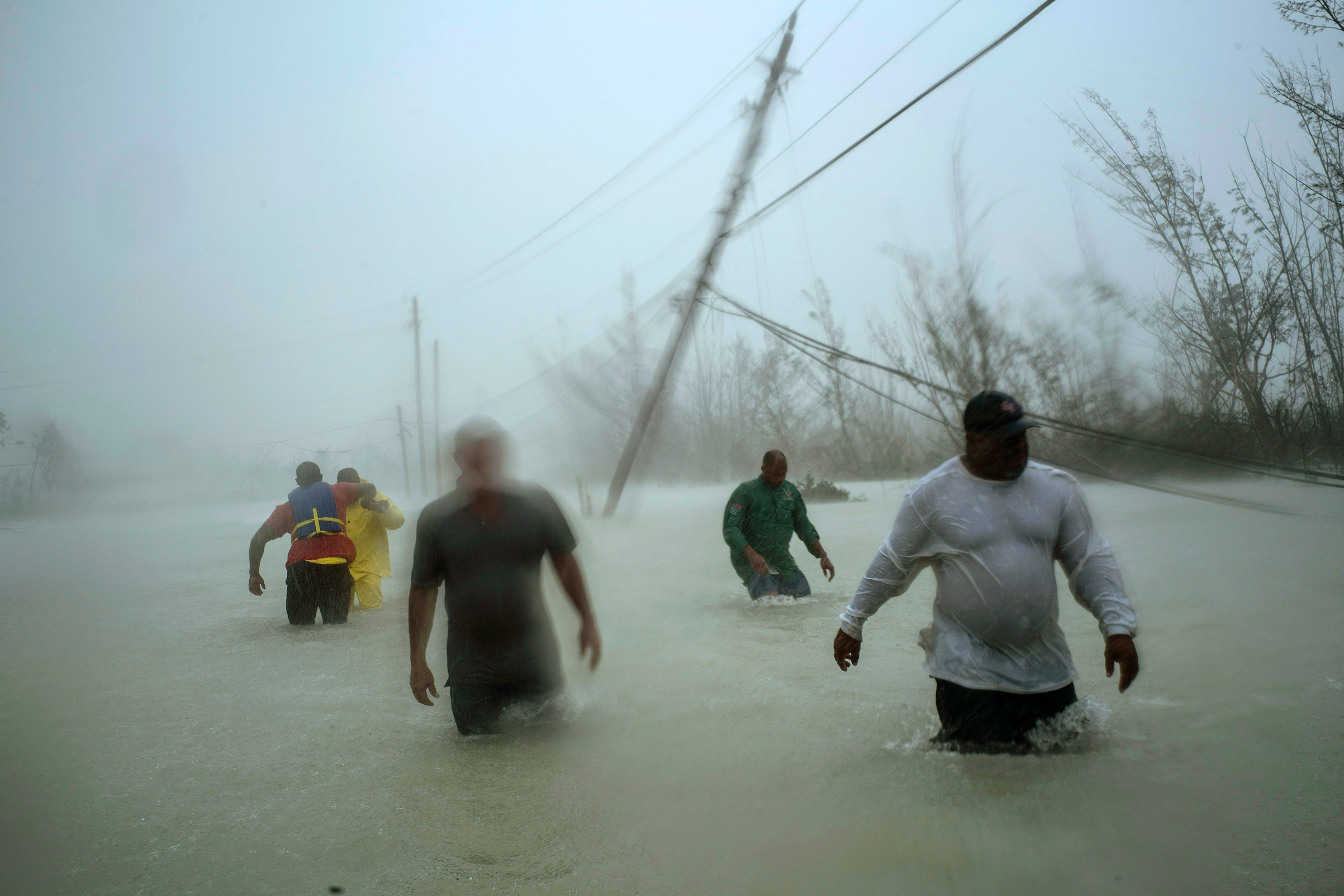Volunteers wade through a flooded road against wind and rain caused by Hurricane Dorian to rescue families near the Causarina bridge in Freeport, Grand Bahama, Bahamas, Sept. 3, 2019. The storm's winds and muddy floodwaters devastated thousands of homes, crippled hospitals and trapped people in attics.