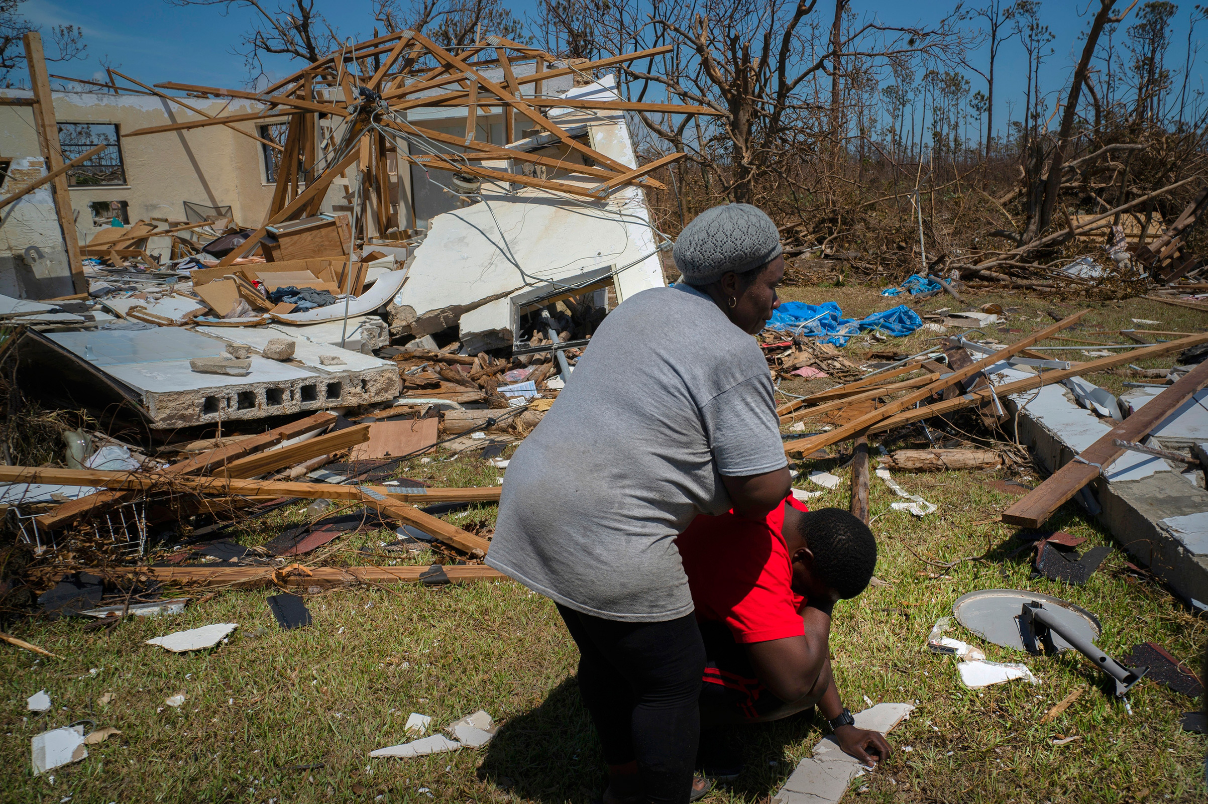 A woman comforts a man who cries after discovering his shattered house and not knowing anything about his eight missing relatives who lived there, High Rock, Grand Bahama, Bahamas, Thursday, Sept. 5, 2019.