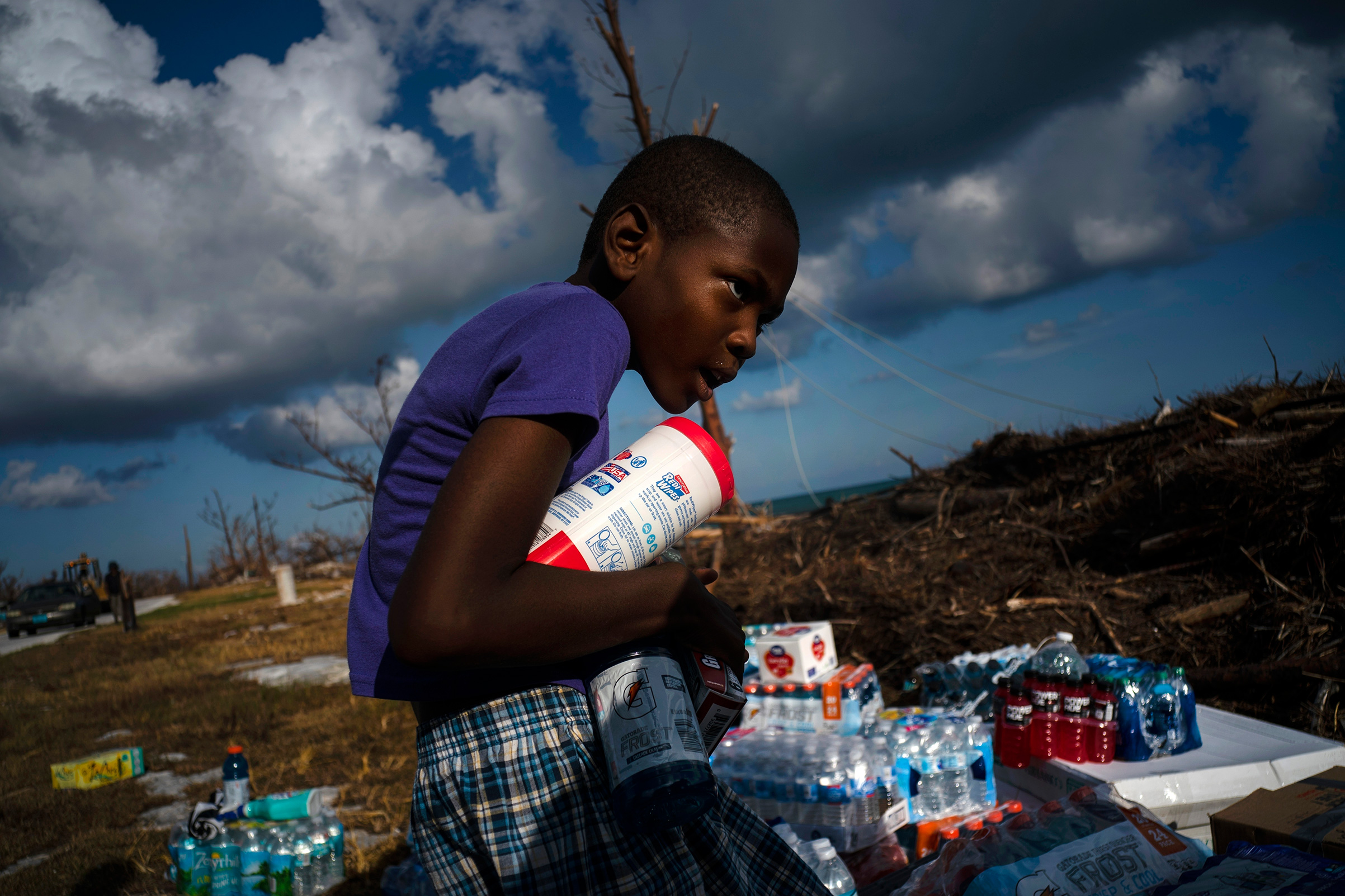 Ayfon Minus, 8, collects donated food that was brought by helicopter from Freeport to the Hurricane Dorian destroyed village of High Rock, Grand Bahama, Bahamas, Sept. 10, 2019.