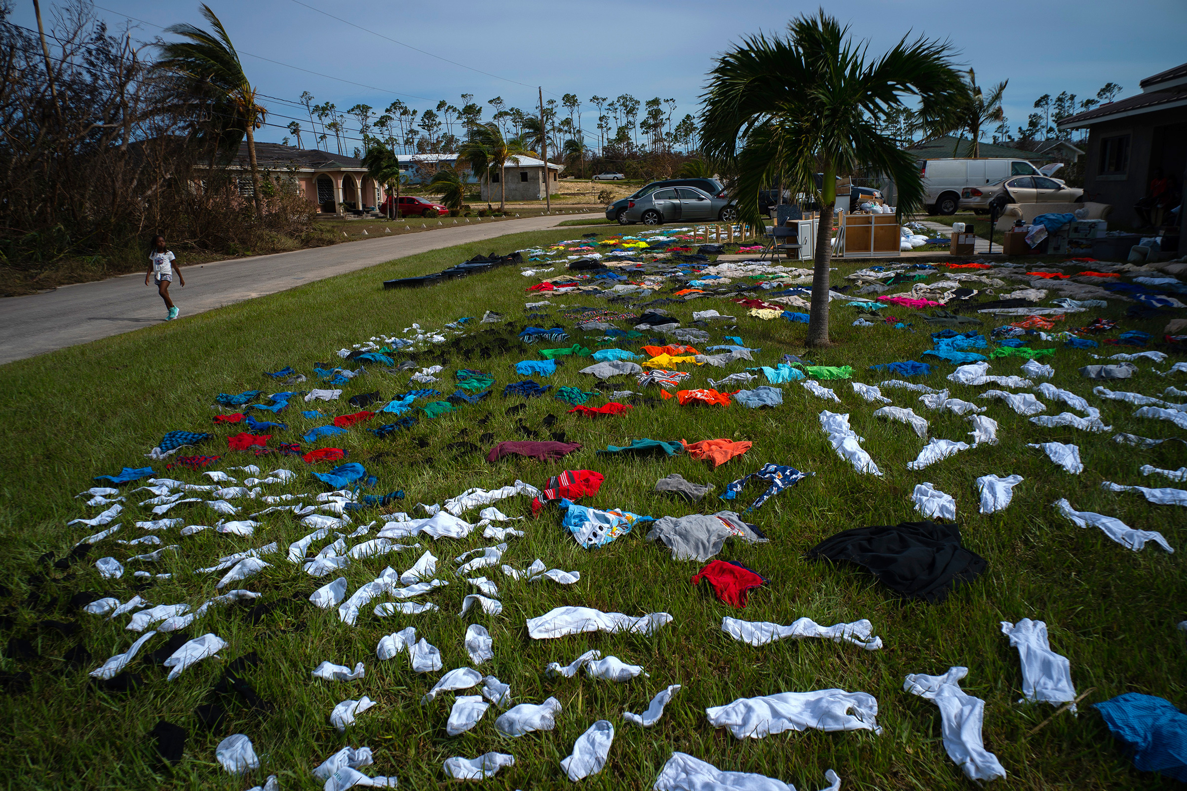 A child walks past clothes laid out to dry on a field in the aftermath of Hurricane Dorian in the Arden Forest neighborhood of Freeport, Bahamas, Sept. 4, 2019.