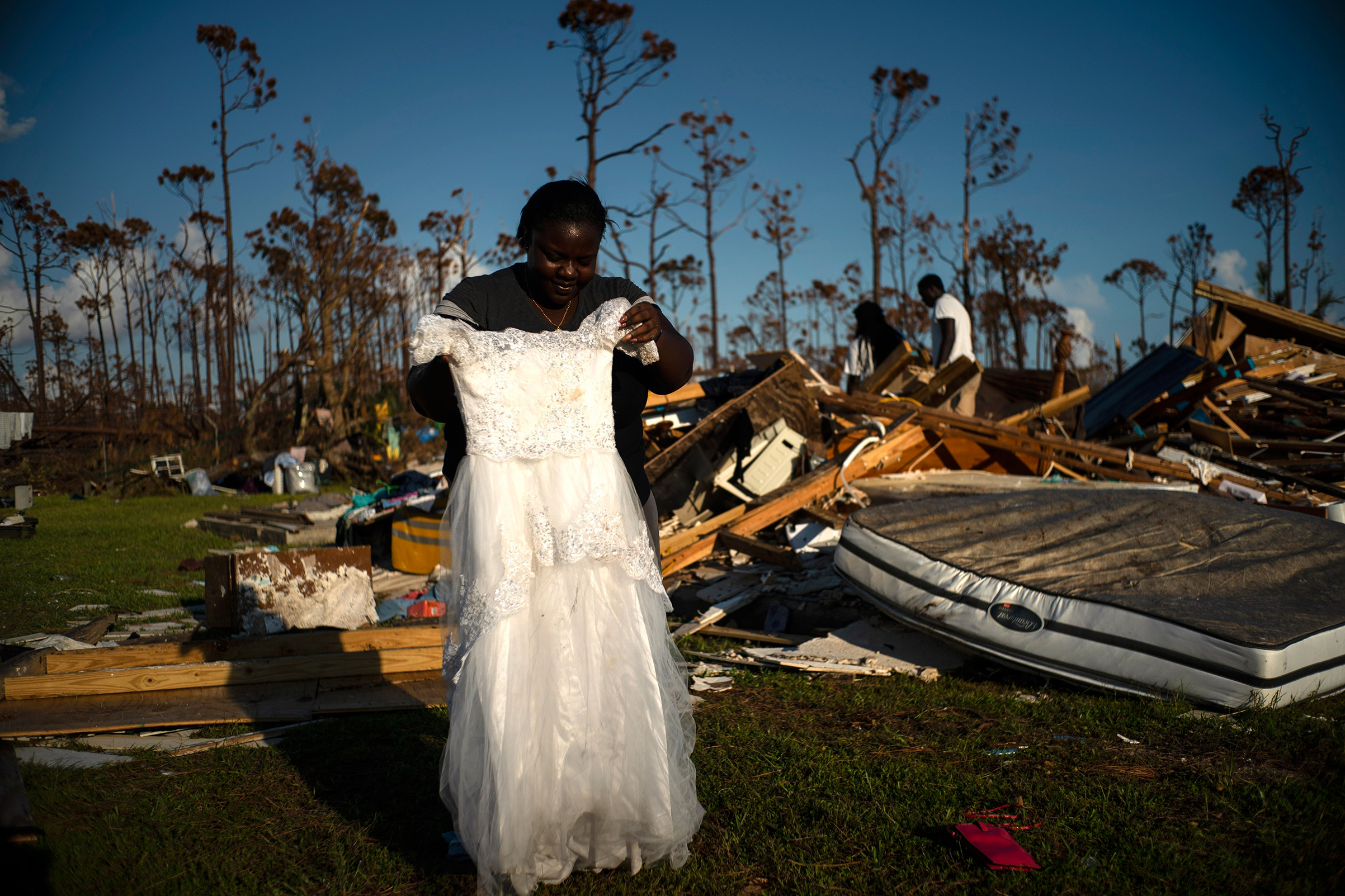 Synobia Reckley holds up the dress her niece wore as a flower girl at her wedding, as she goes through valuables in the rubble of her home destroyed one week ago by Hurricane Dorian in Rocky Creek East End, Grand Bahama, Bahamas, Sept. 8, 2019.