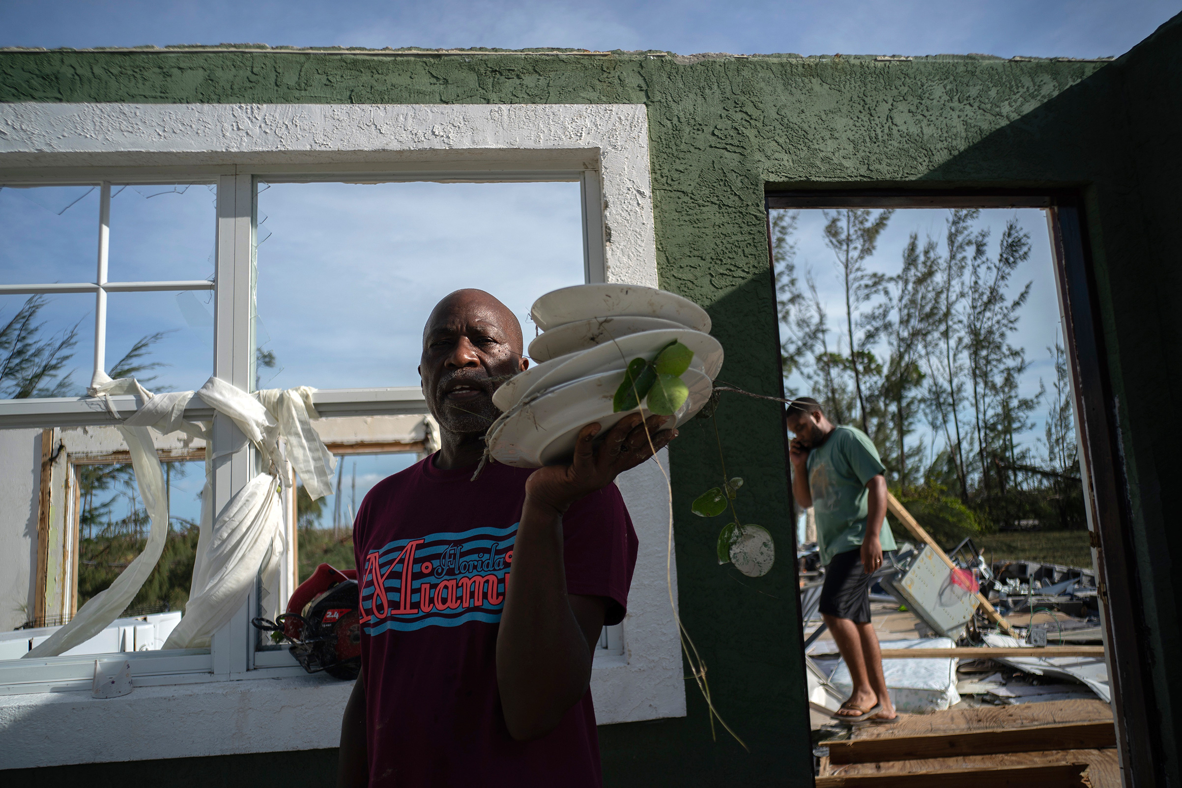 Mister Bolter recovers dishes from his son's home, destroyed by Hurricane Dorian in Pine Bay, near Freeport, Bahamas, Wednesday, Sept. 4, 2019.