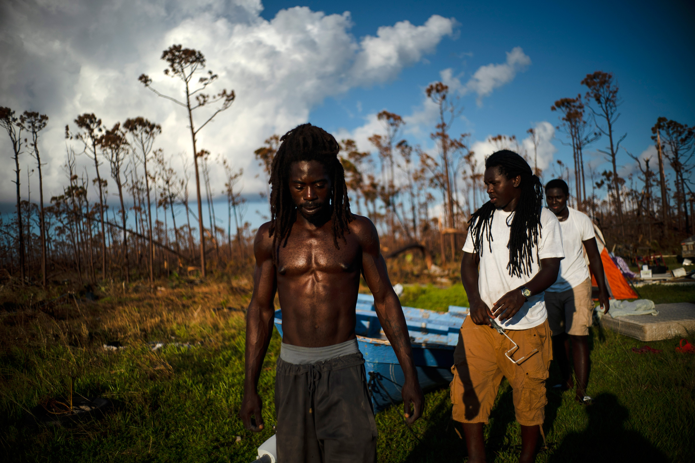 Dexter Edwards, front, his brother Nathanael Edwards right, and his cousin Valentino Ingraham walk amid one of their family's homes destroyed by Hurricane Dorian in Rocky Creek East End, Grand Bahama, Bahamas, Sept. 8, 2019.  Right now, ain't much joy. You just gotta try to keep your head up,  Edwards said.  There's always a future. Only thing we can do right now is rebuild-rebuild and try to move forward.