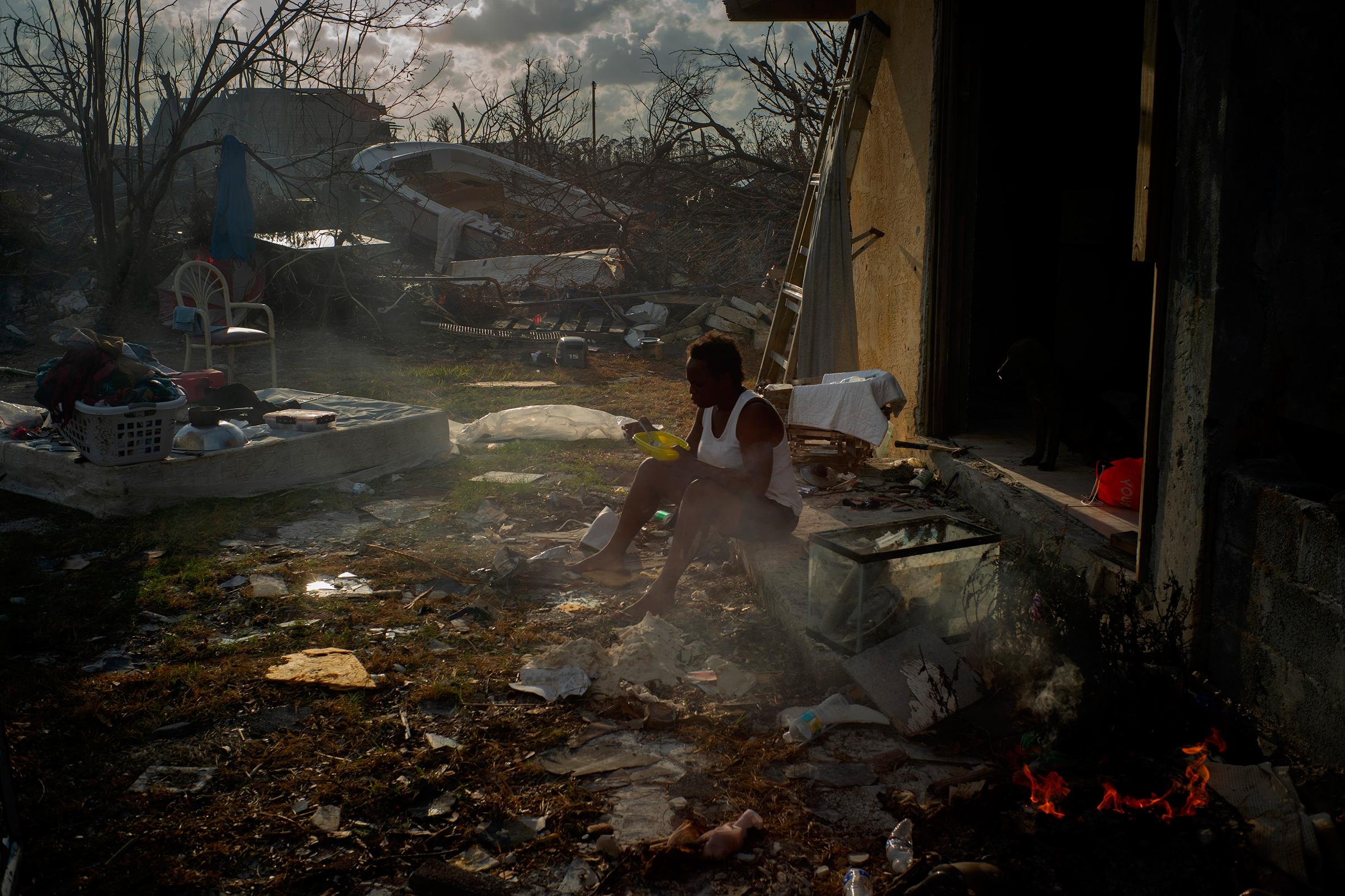 Tereha Davis, 45, eats a meal of rice as she sits among the remains of her shattered home, in the aftermath of Hurricane Dorian in McLean's Town, Grand Bahama, Bahamas, Sept. 11, 2019. She and others said they had not seen any government officials and have only received food and water from nonprofit organizations.