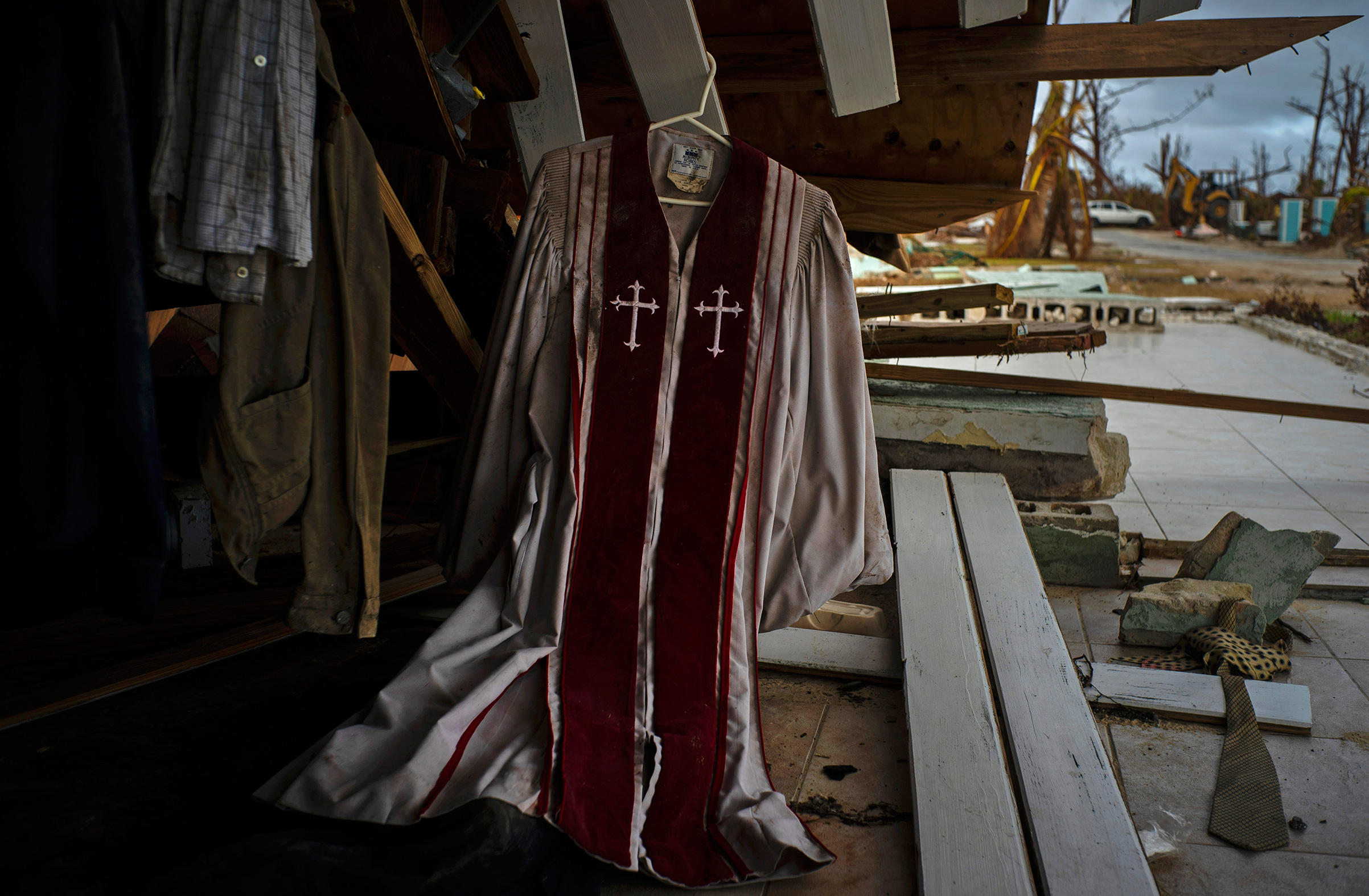 Priest's mass vestments hang in the rubble of a destroyed house by Hurricane Dorian in Pelican Point, Grand Bahama, Bahamas, Sept. 14, 2019.