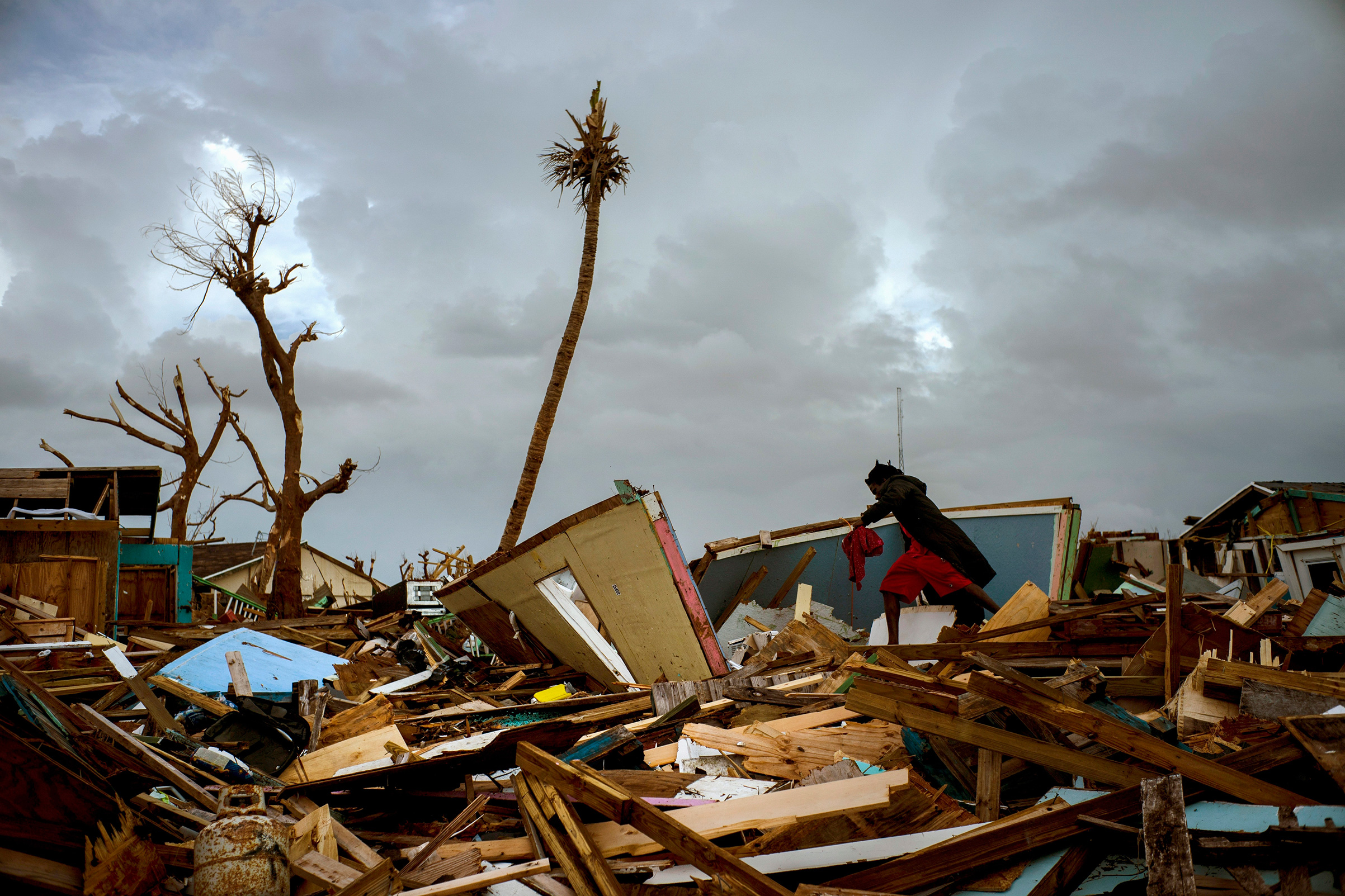 Vladimir Safford an immigrant from Haiti walks through the rubble near his home Abaco, Bahamas, Sept. 16, 2019.