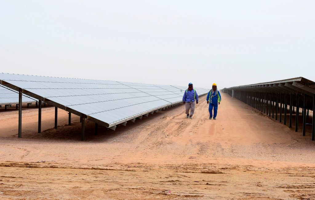 Employees walk past solar panels at the Mohammed bin Rashid Al-Maktoum Solar Park on March 20, 2017, in Dubai.