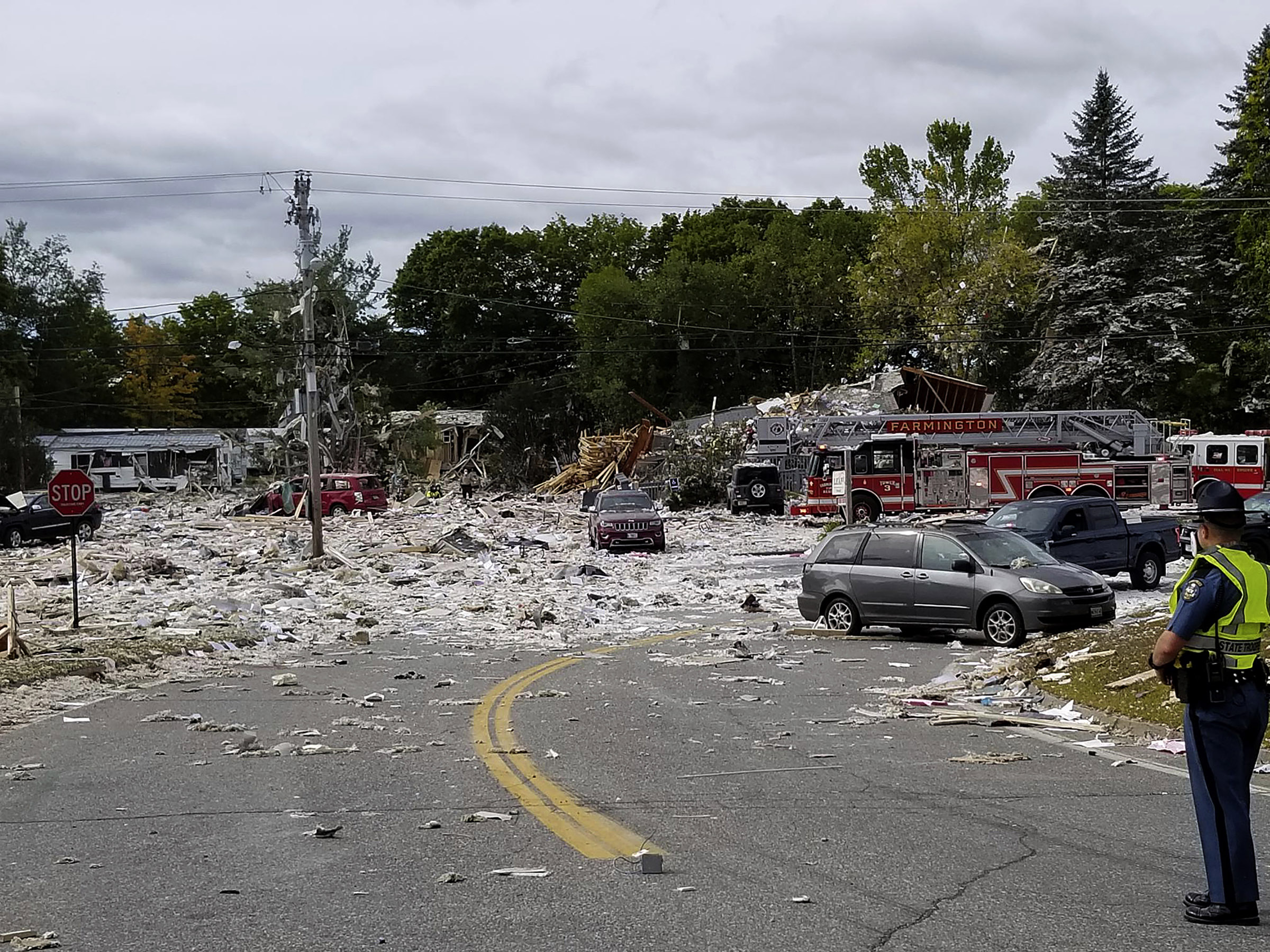 A police officer stands guard on Sept. 16, 2019, at the scene of a deadly propane explosion which leveled new construction in Farmington, Maine.
