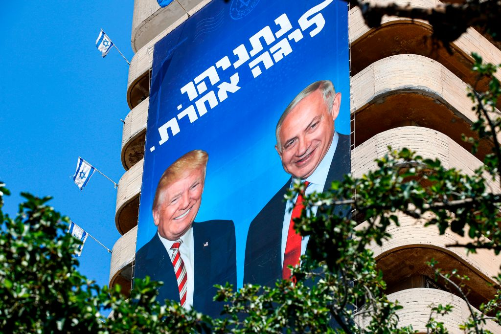 Two giant Israeli Likud Party election banners hanging from a Tel Aviv building show Israeli Prime Minister Benjamin Netanyahu shaking hands with U.S. President Donald Trump, with a caption above reading in Hebrew  Netanyahu, in another league