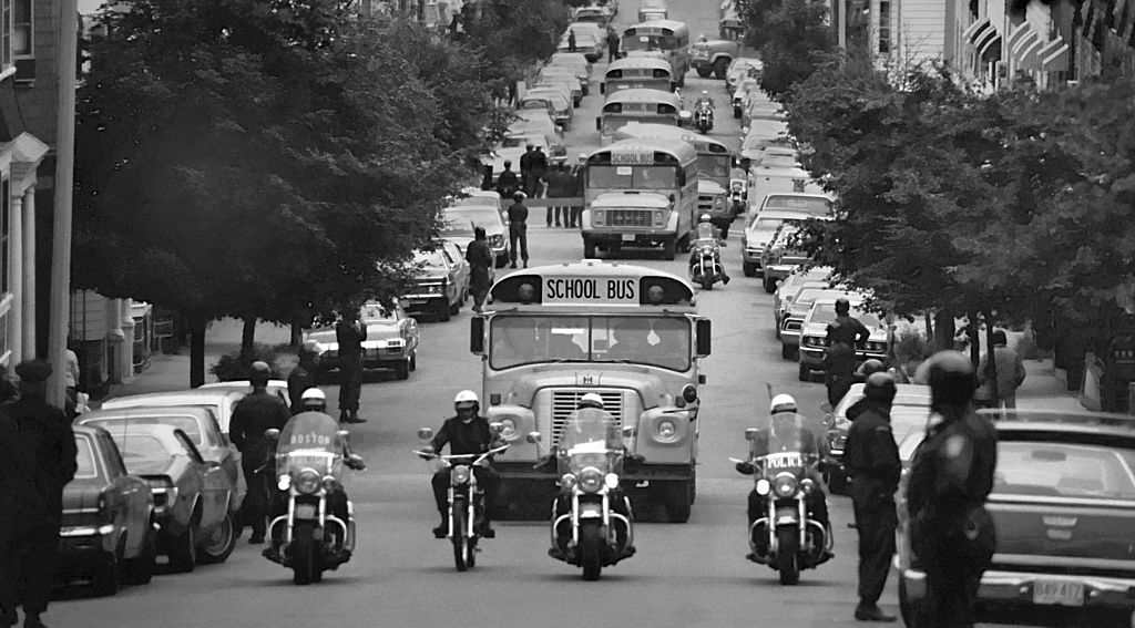 Accompanied by motorcycle-mounted police, school buses carrying African American students arrive at formerly all-white South Boston High School on September 12, 1974. In 1971, the U.S. Supreme Court ruled in favor of busing as a mechanism to end racial segregation because black children were still attending segregated schools. White children had been riding school buses for decades, but the idea of using the same mechanism to desegregate public schools triggered violent protests, writes Gloria J. Browne-Marshall.