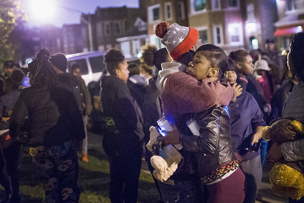 A mourner embraces Pierre Stokes, the father of 9-year-old Tyshawn Lee, during a candlelight vigil held outside his home in memory of his son on November 5, 2015 in Chicago.