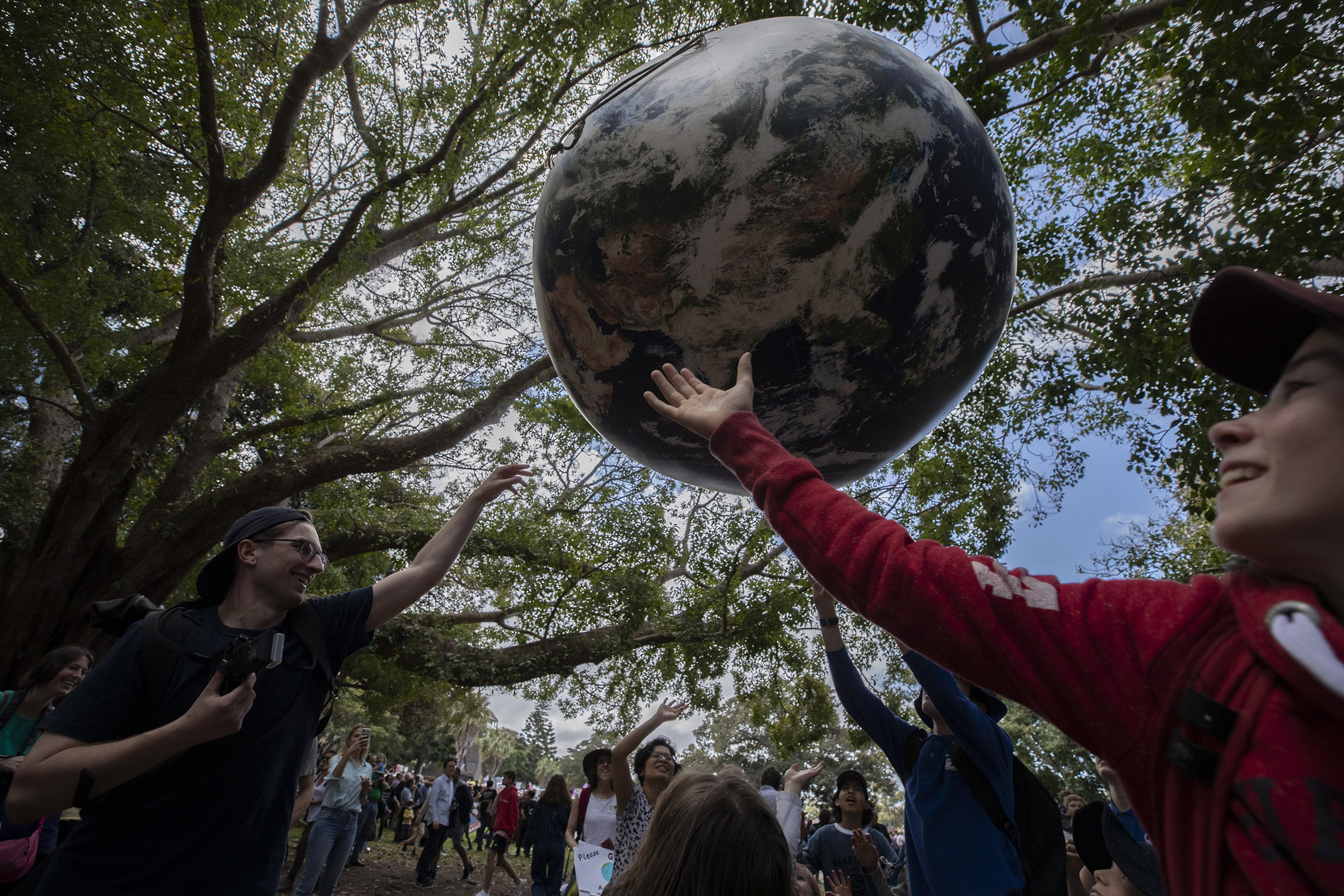 Young protestors play with a large globe on September 20, 2019 in Sydney, Australia. Rallies held across Australia are part of a global mass day of action demanding action on the climate crisis. (