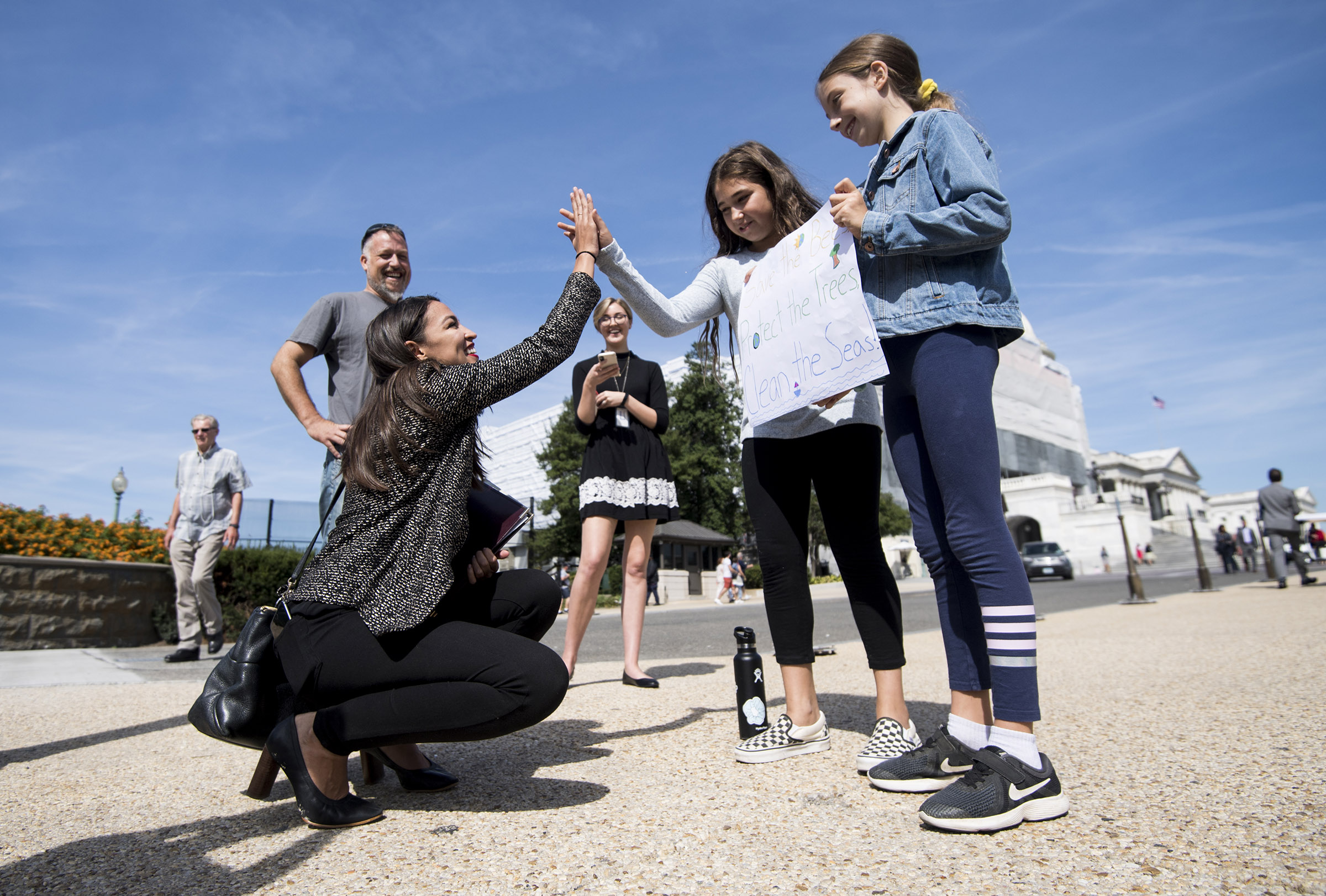 Rep. Alexandria Ocasio-Cortez, D-N.Y., high-fives climate striking students Evelyn Seek, center, and Pema Duncan, right, as they hold their climate strike sign in front of the Capitol on Friday, Sept. 20, 2019.