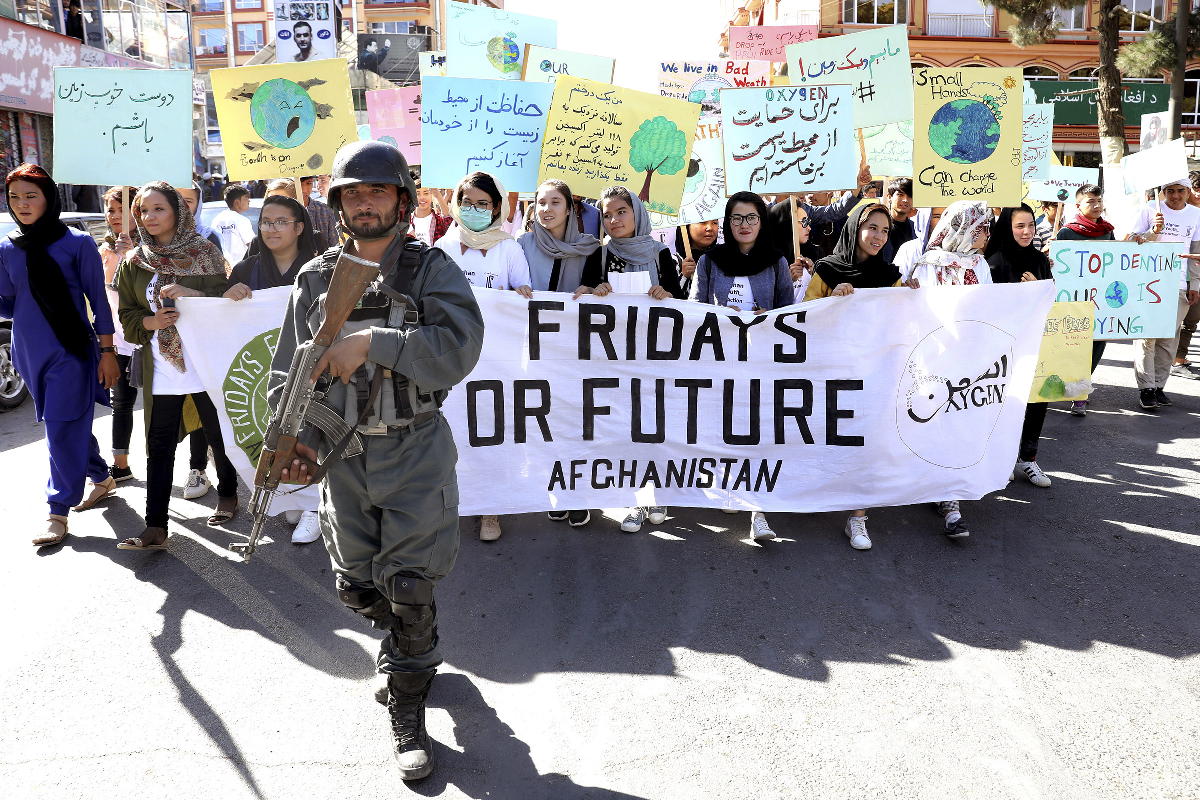 Young people attend a Climate Strike rally, as Afghan security forces guard them in Kabul, Afghanistan, Friday, Sept. 20, 2019.