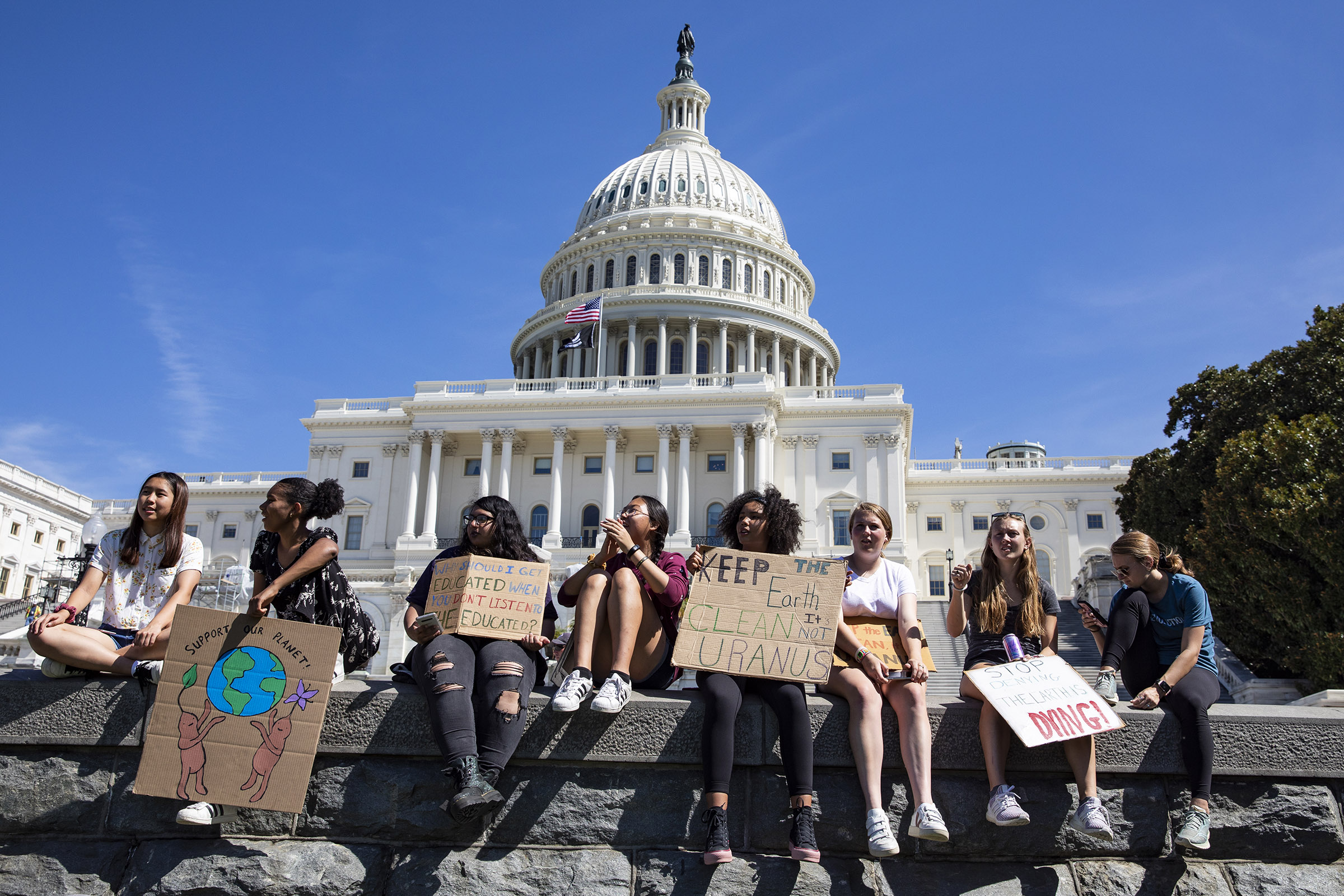 Teens sit along a wall at the U.S. Capitol during the Global Climate Strike rally on September 20, 2019 in Washington, DC.