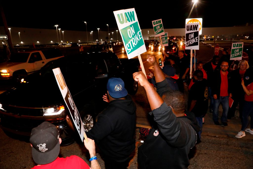 Members of the United Auto Workers (UAW) who are employed at the General Motors Co. Flint Assembly plant in Flint, Michigan, hold signs and cheer as workers drive out of the plant as they go on strike early on September 16, 2019.