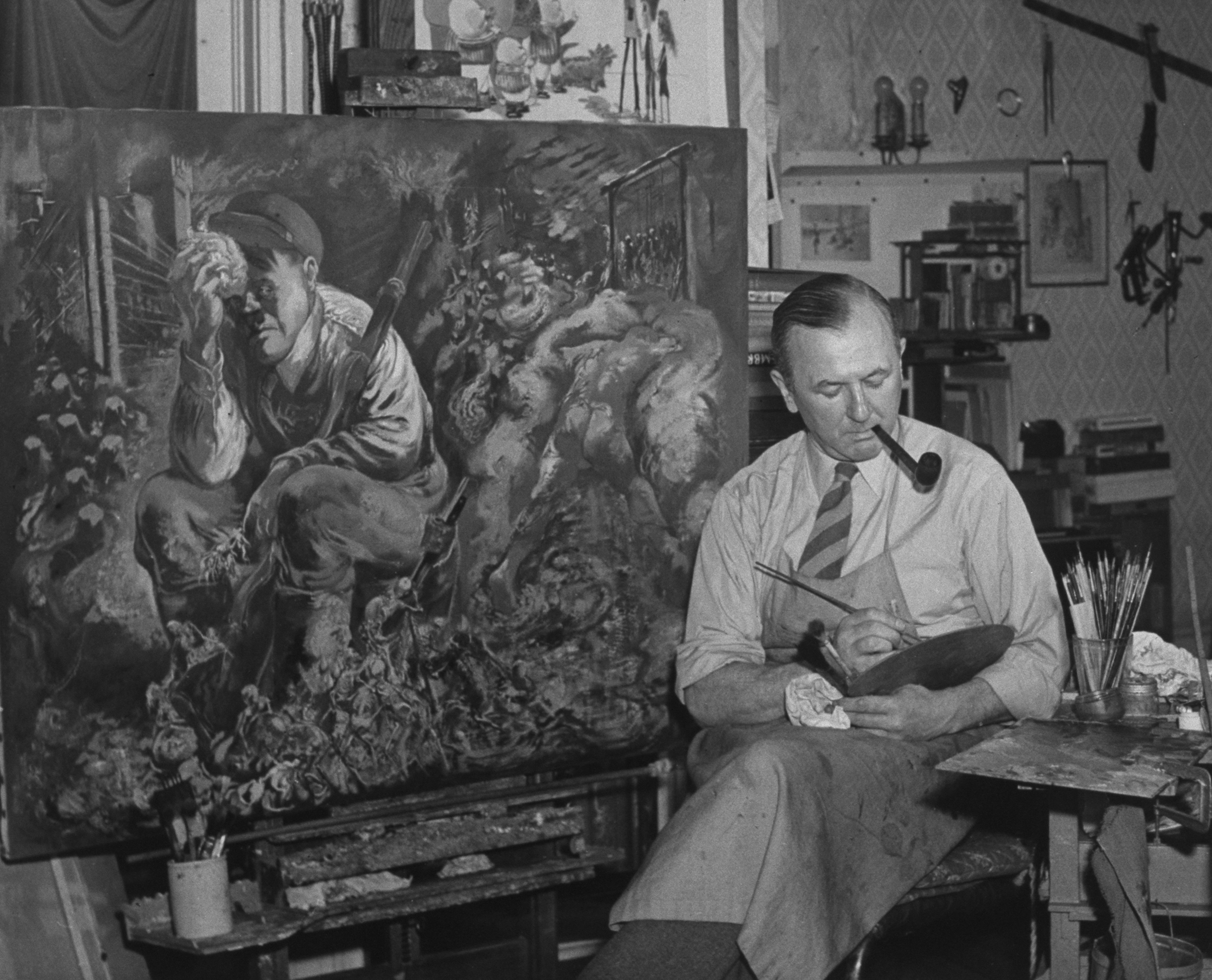 German-born painter George Grosz working on a satirical painting that depicts Adolf Hitler resting with skeletons at his feet, in studio at home