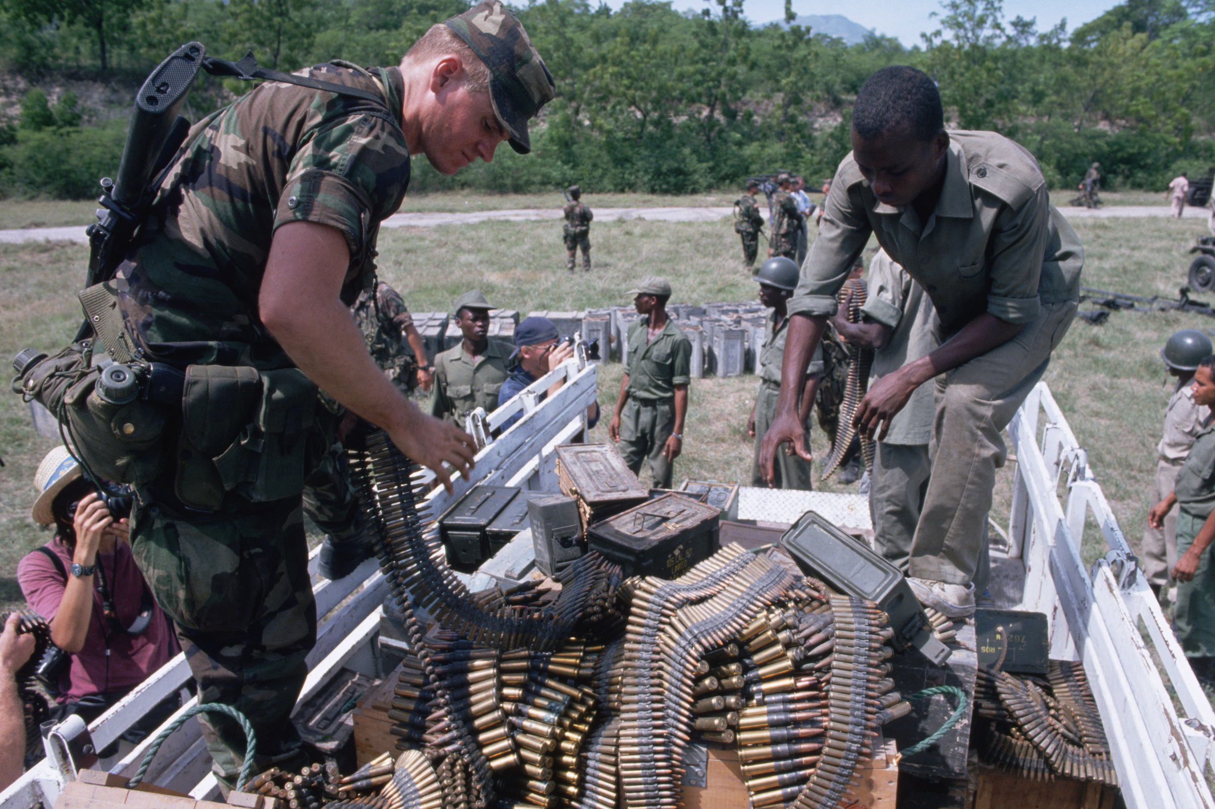 An American and Haitian soldier unload ammunition together from a supply truck in 1994.