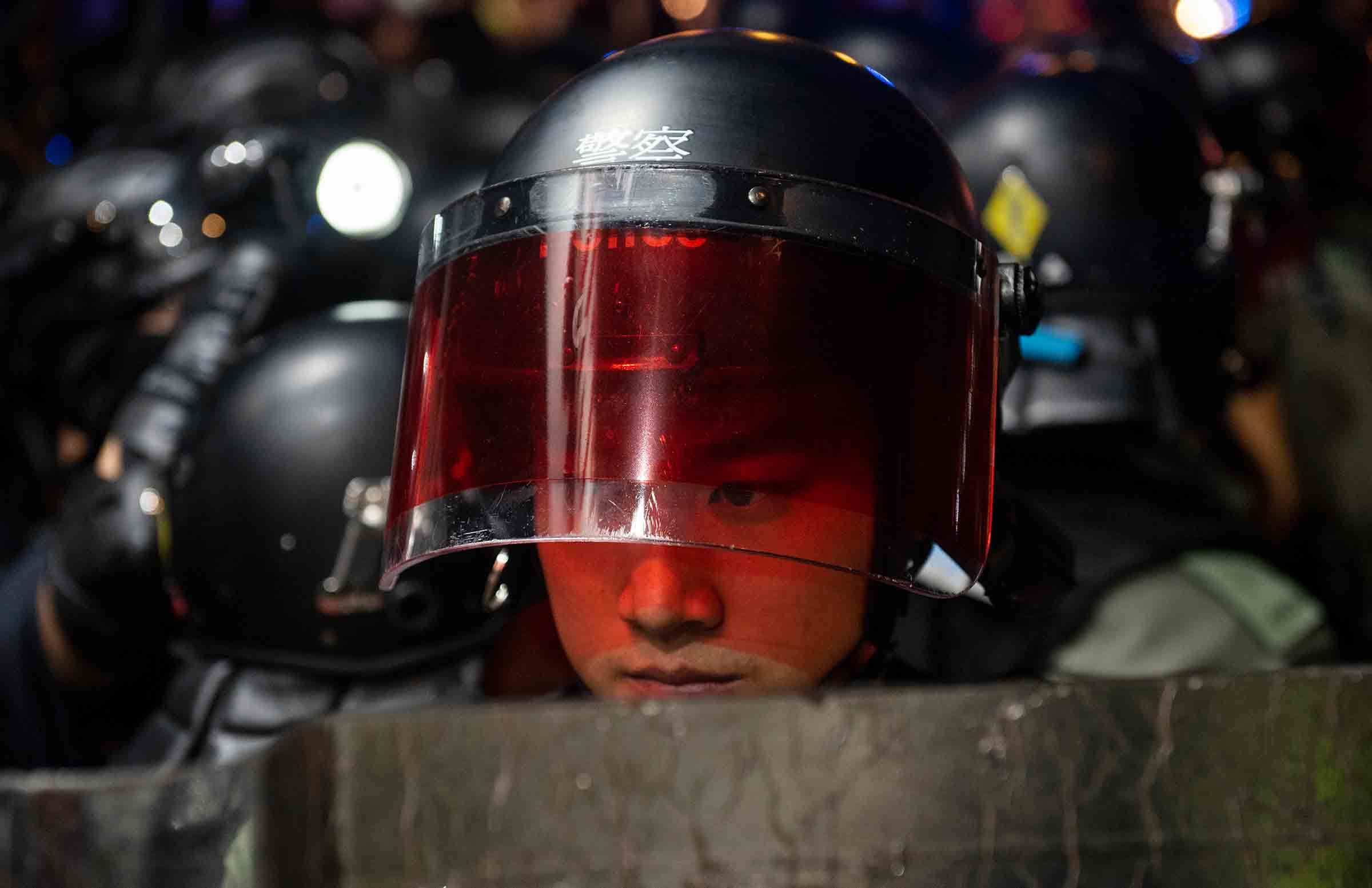 A riot-police officer watches protesters in Hong Kong on Sept. 21