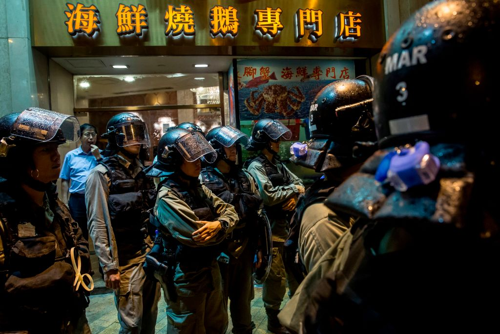 Riot police stand in front of a restaurant while patrolling after an anti-government rally in Hong Kong on August 18, 2019.