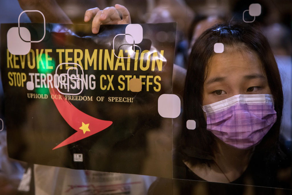 Protesters stick posters and notes on the outside of Cathay Pacific offices during a rally against the dismissal of Cathay Pacific staff in Hong Kong on August 28, 2019.