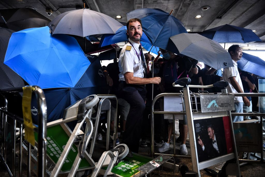 An airline crew member makes his way through a barrier set up by protesters at Hong Kong International Airport on September 1, 2019. - Hundreds of Hong Kong pro-democracy activists attempted to block transport routes to the city's airport on September 1, as the financial hub began cleaning up after another night of serious violence marked by fires, tears gas and police beatings. (Photo by Lillian SUWANRUMPHA / AFP)        (Photo credit should read LILLIAN SUWANRUMPHA/AFP/Getty Images)
