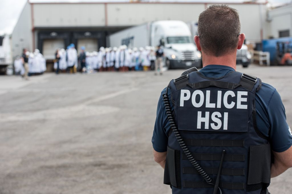 Homeland Security Investigations (HSI) special agent preparing to arrest alleged immigration violators at Fresh Mark, Salem, June 19, 2018. Image courtesy ICE ICE / U.S. Immigration and Customs Enforcement.