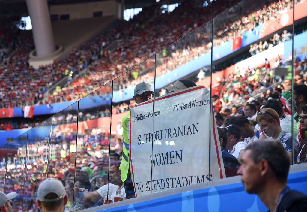 Iran's soccer fans hold a sign calling for Iranian women to be let into sports stadiums during the 2018 FIFA World Cup game between Morocco and Iran at Saint Petersburg Stadium on June 15, 2018.