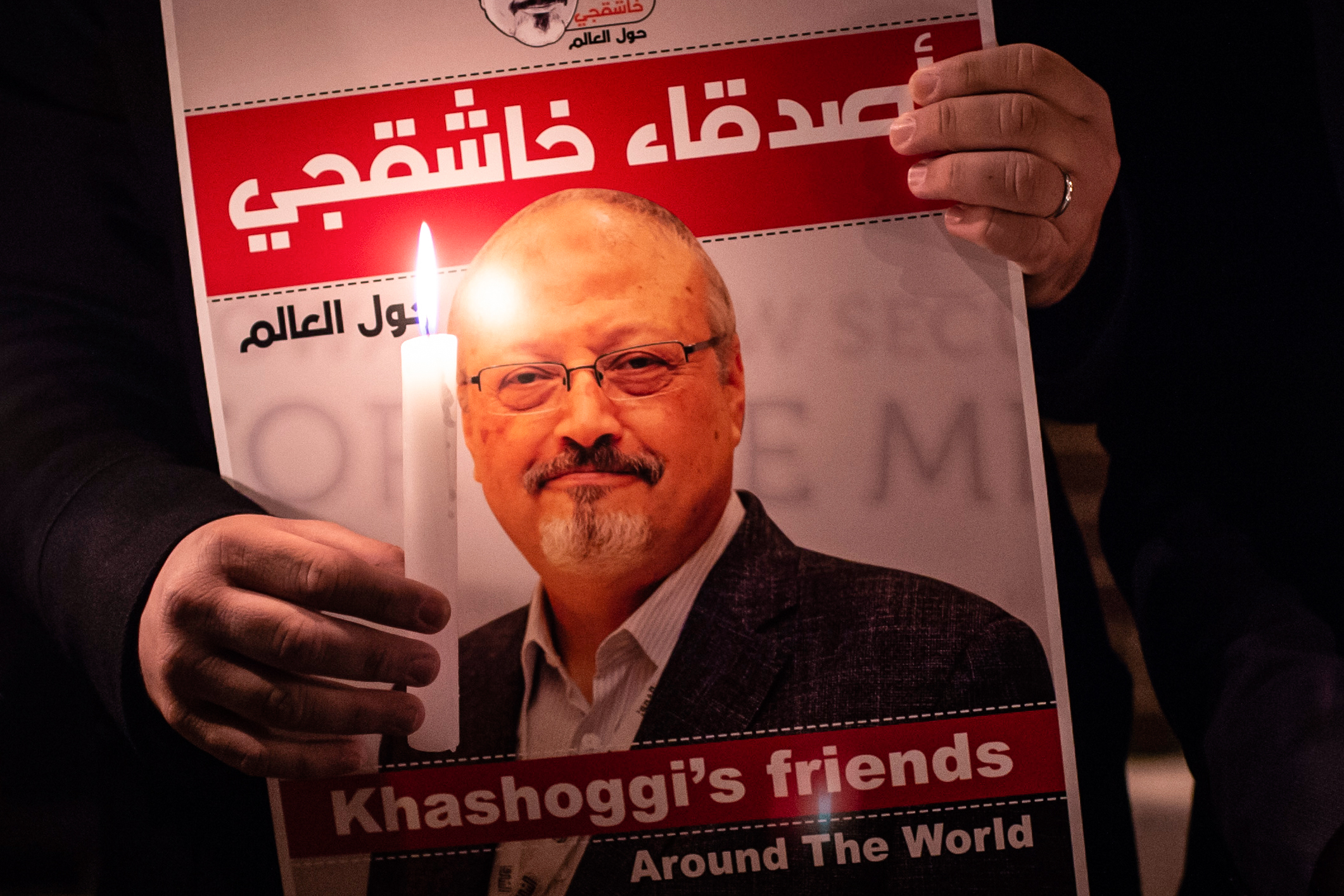 TOPSHOT - A demonstrator holds a poster picturing Saudi journalist Jamal Khashoggi and a lightened candle during a gathering outside the Saudi Arabia consulate in Istanbul, on October 25, 2018. - Jamal Khashoggi, a Washington Post contributor, was killed on October 2, 2018 after a visit to the Saudi consulate in Istanbul to obtain paperwork before marrying his Turkish fiancee. (Photo by Yasin AKGUL / AFP)        (Photo credit should read YASIN AKGUL/AFP/Getty Images)