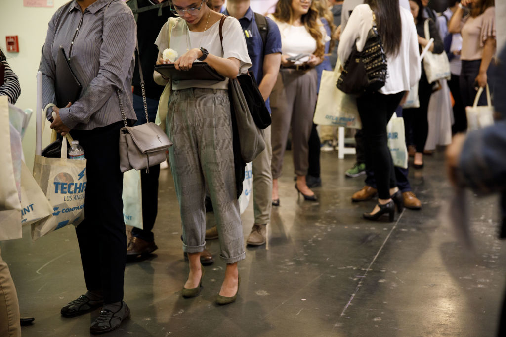 Job seekers wait in line to speak with representatives during the TechFair LA career fair in Los Angeles, California, U.S., on Thursday, March 8, 2018.