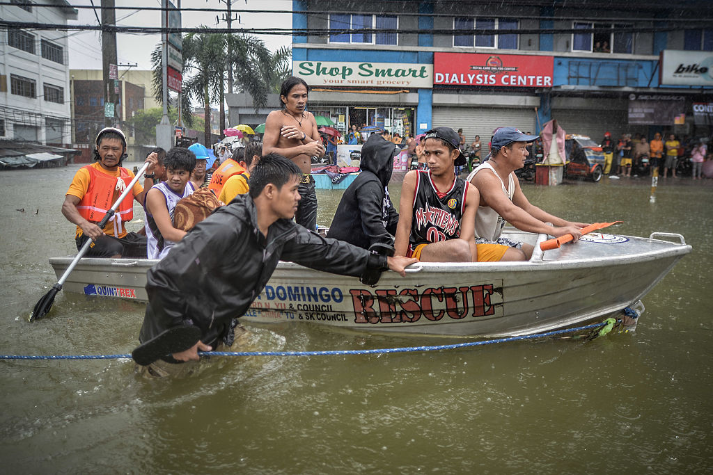 Flood victims are evacuated in a rescue boat after their homes were swamped by heavy flooding in Quezon city, suburban Manila, Philippines, Sept. 19, 2014.
