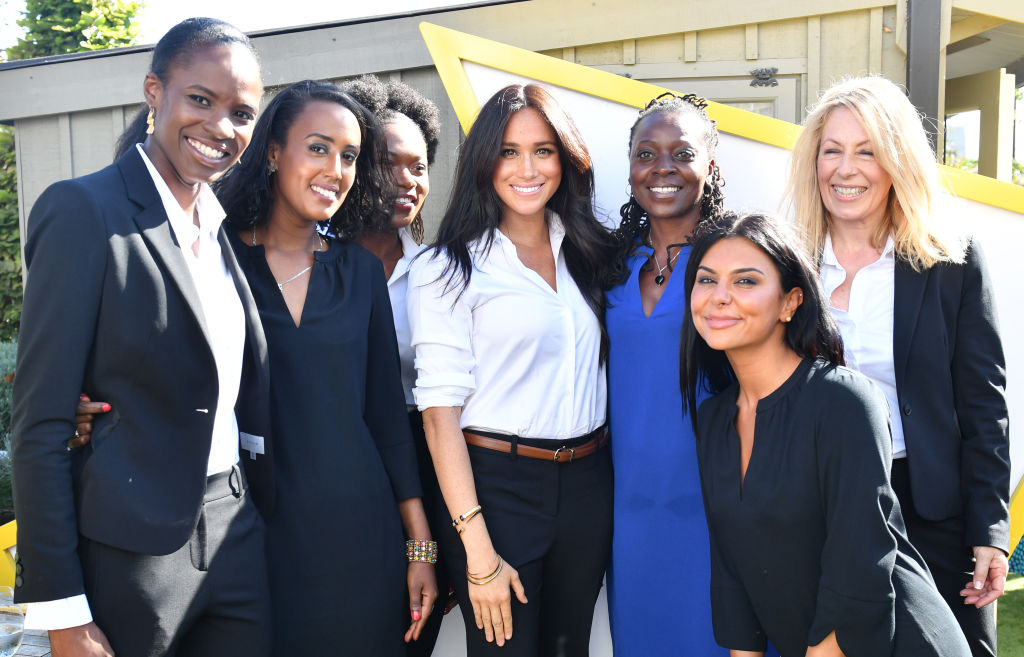 Meghan, Duchess of Sussex poses for a photograph with women dressed in clothes from the Smart Works capsule collection during the collection's launch on September 12, 2019 in London, England.