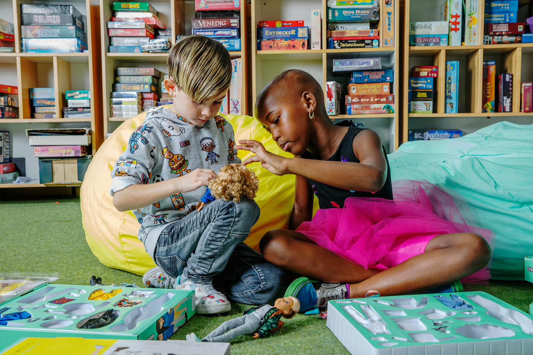 Shi'a, left, and Jhase play with Mattel's gender-neutral doll