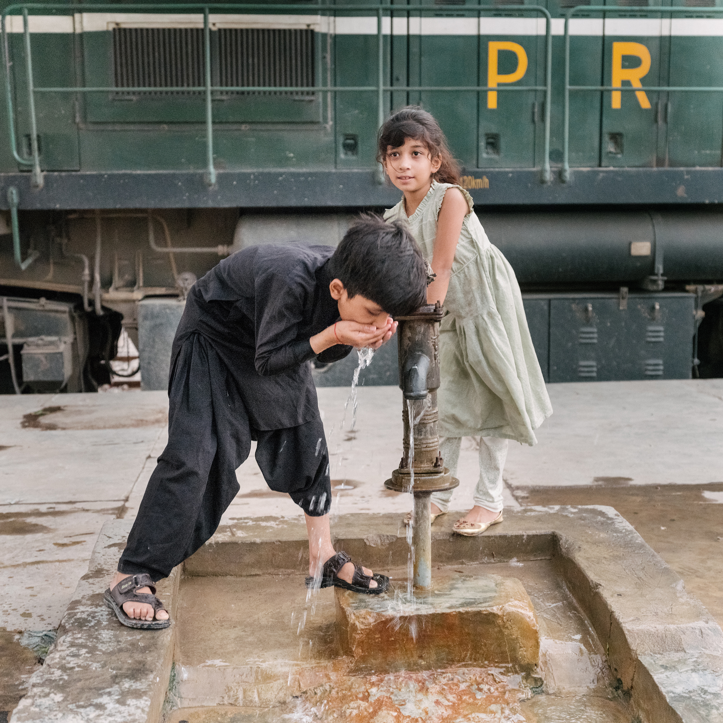 A brother and sister have a drink of water during an evening outing at the train station on June 28.
