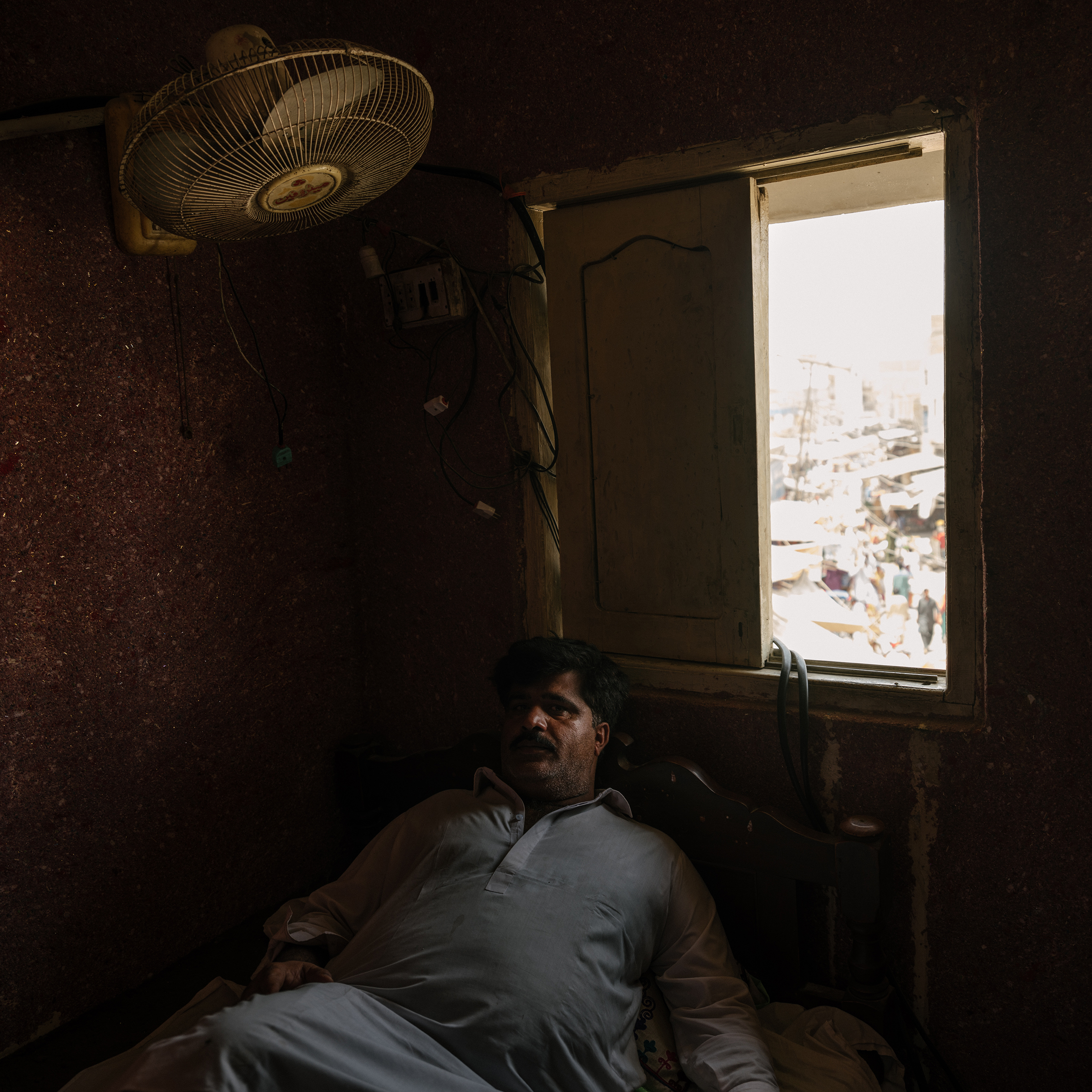 Seraj Udin, owner of the Greenland Hotel in Jacobabad, takes a break during a rolling blackout on June 30.