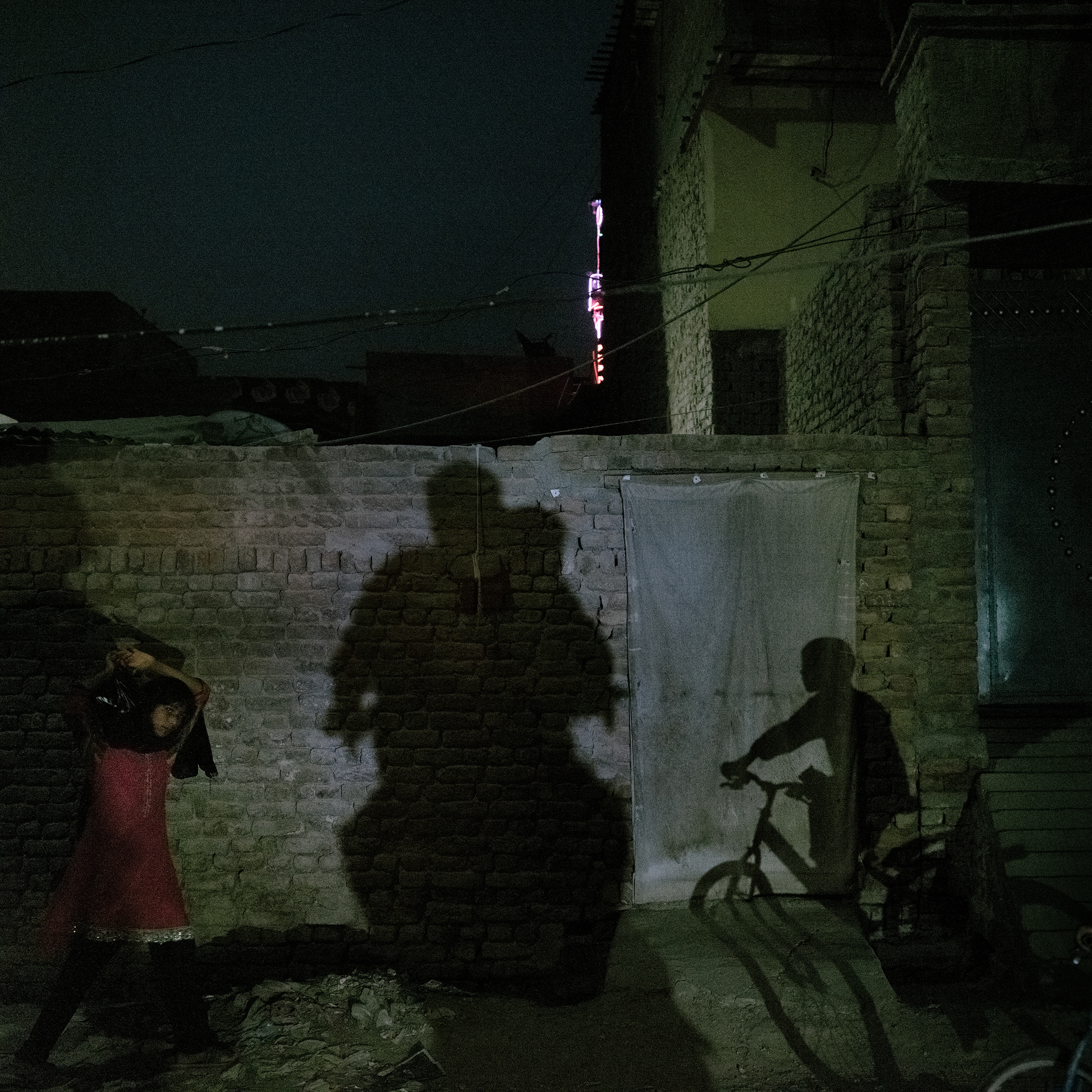 A range of activities happens at night in Jacobabad on June 27: a girl returns home with groceries; a boy rides a bicycle; and a father and son ride home on a motorcycle.