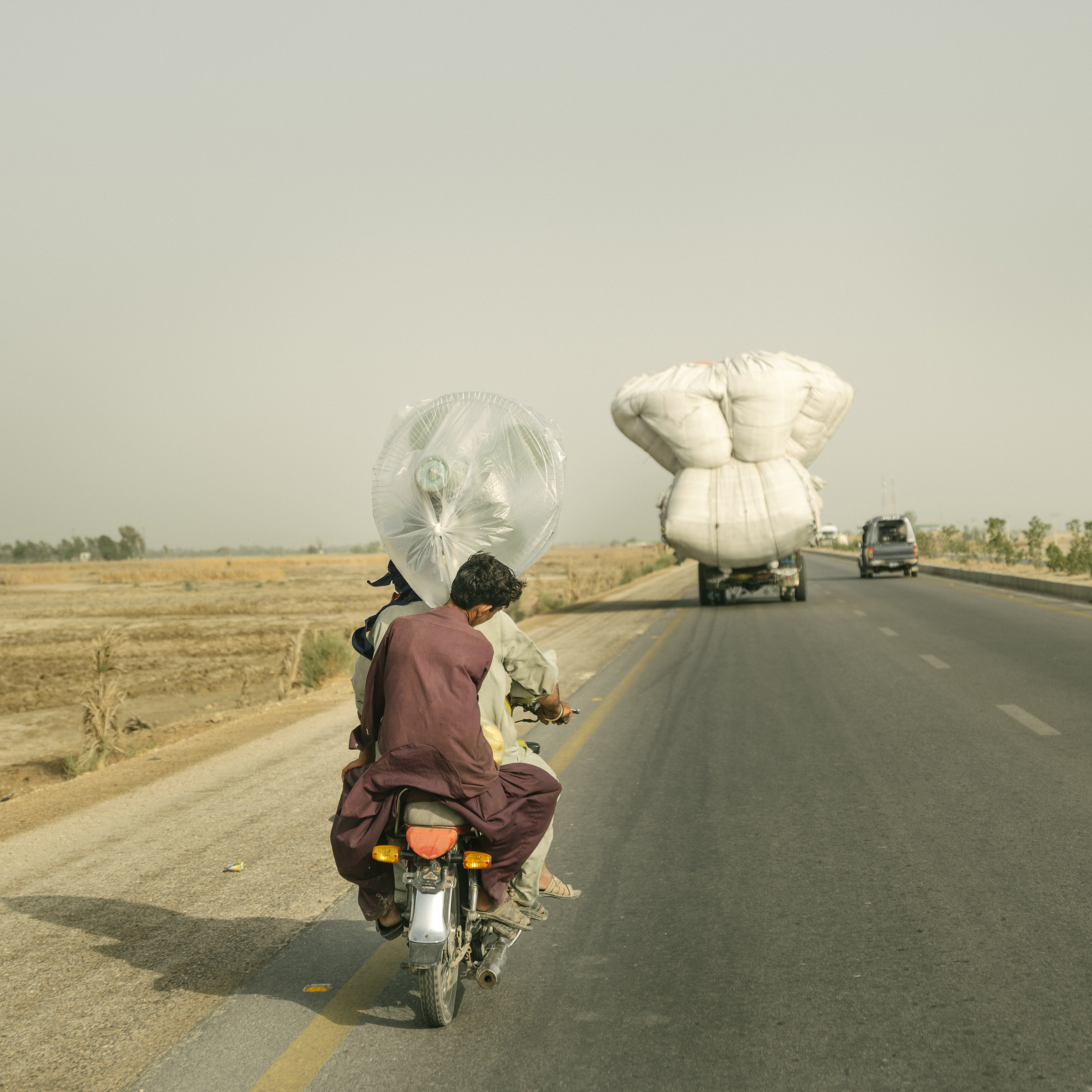 On the outskirts of Jacobabad, men return from a market after purchasing a large fan on June 30.