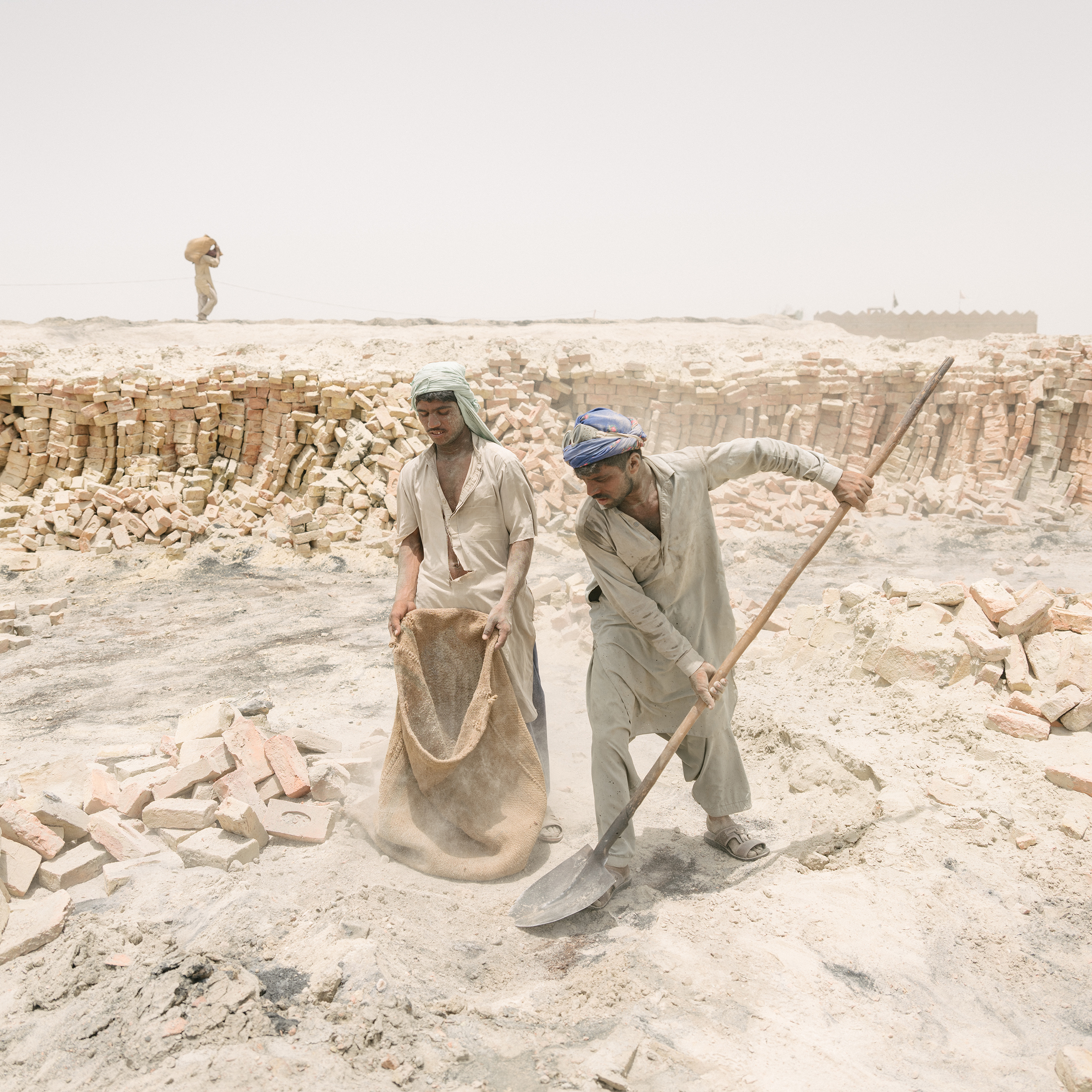 Brick makers fill up a bag of sand on June 29.