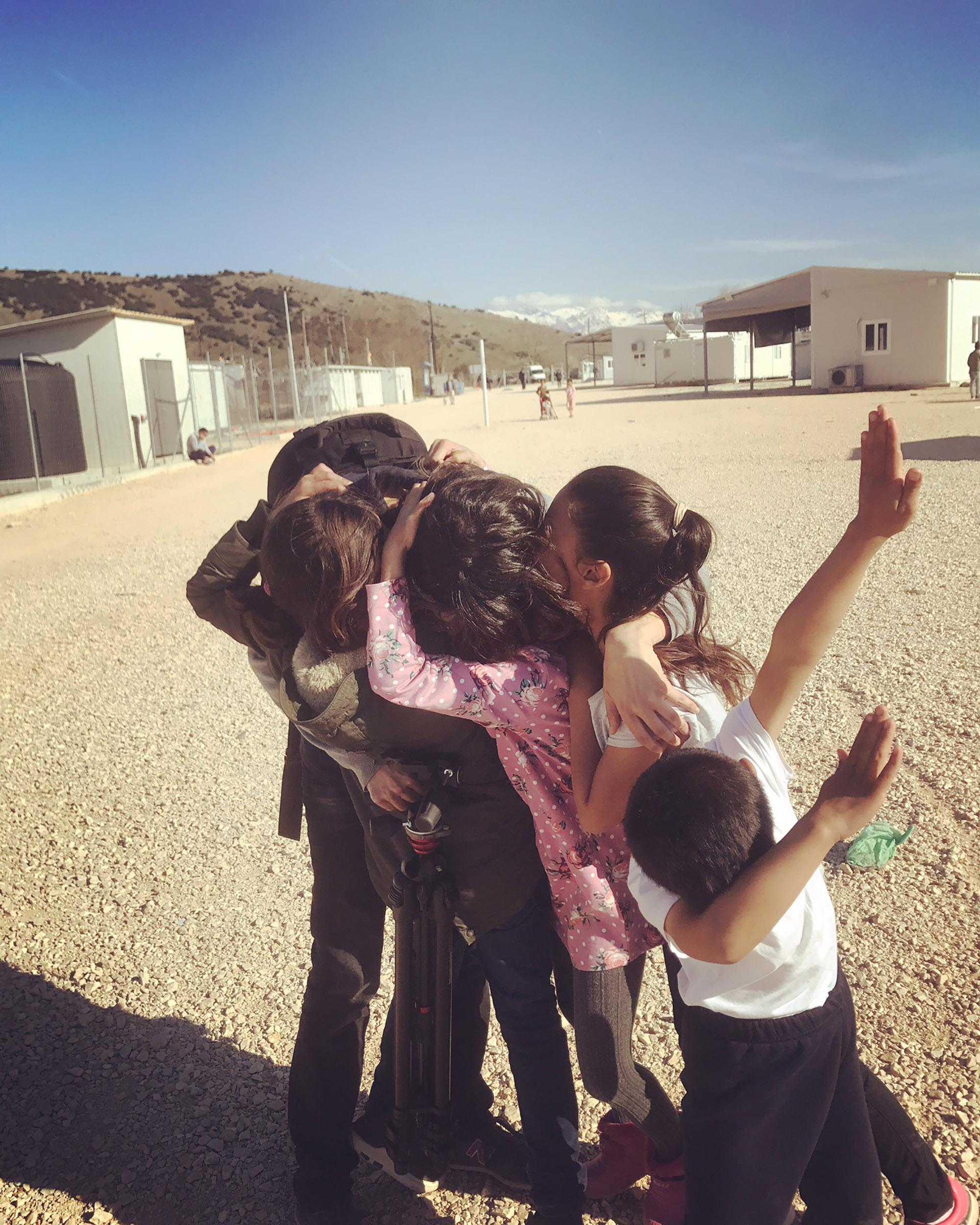 Children hugging photographer Anna Bosch Miralpeix in Katsikas camp in Greece in 2018.