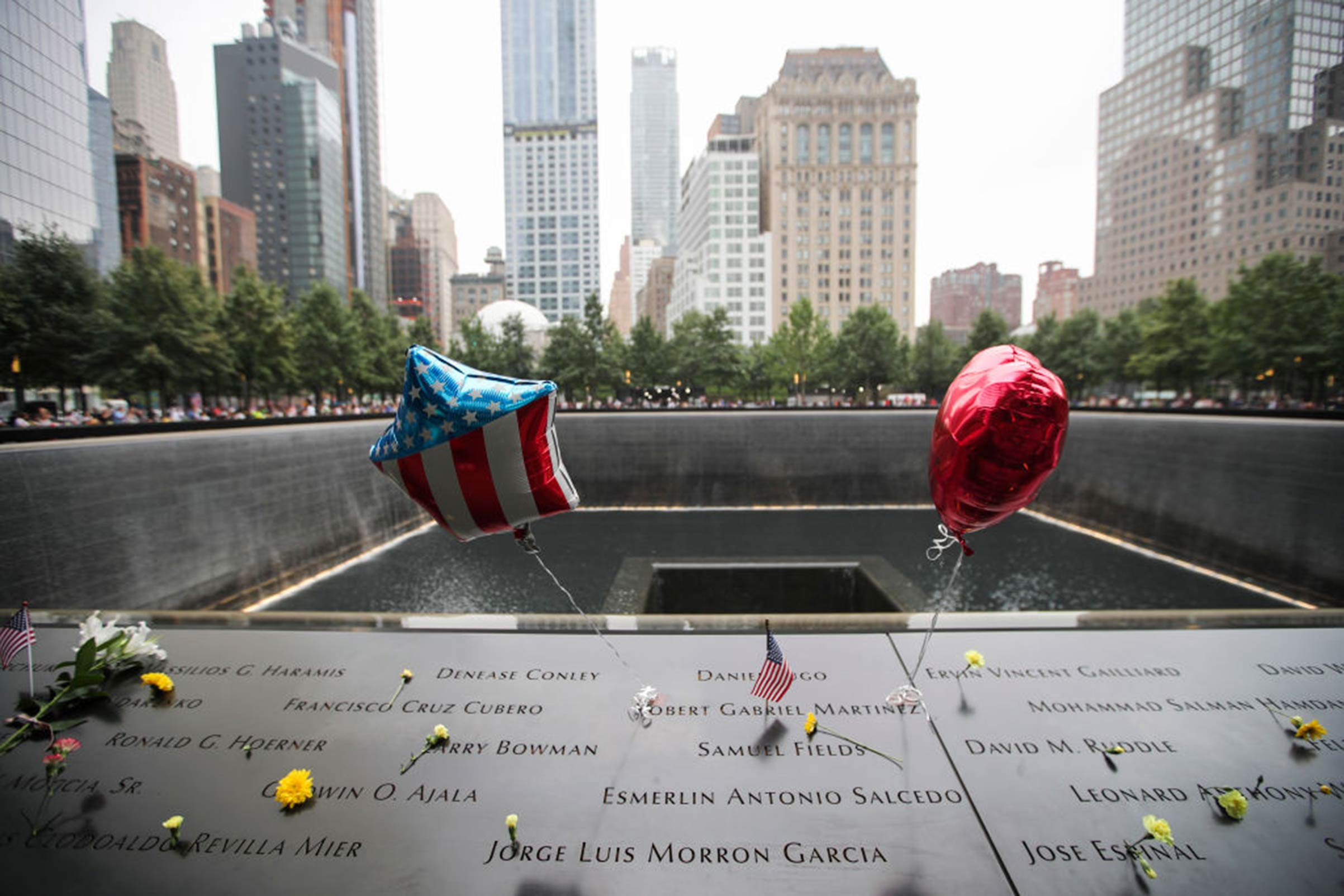 Flowers and balloons are placed on plates on which the names of 9/11 victims were inscribed around the South Pool at the 9/11 Memorial and Museum in New York City on Sept. 11, 2018.