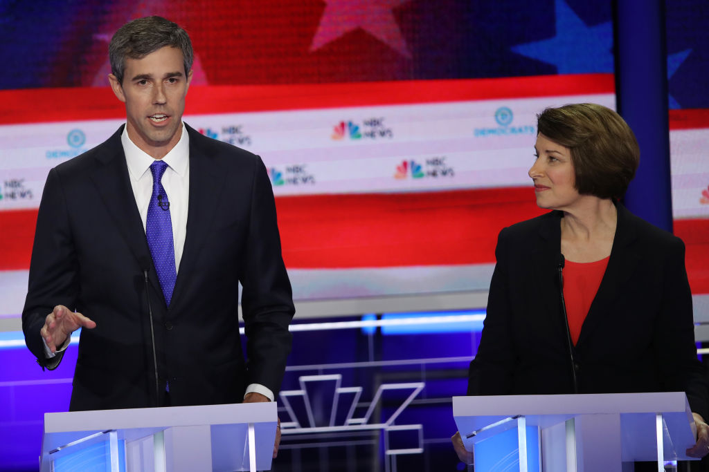 former Texas congressman Beto O'Rourke speaks as Minnesota Sen. Amy Klobuchar looks on during the first night of the Democratic presidential debate on June 26, 2019.