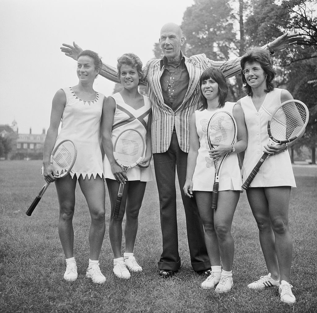 English fashion designer Ted Tinling (1910 - 1990, center), with tennis players wearing his Dacron fashions at the Royal Garden Hotel, Kensington, London, June 22, 1973. Left to right: Virginia Wade of Britain in a dress with shark's teeth details, Evonne Goolagong of Australia in a dress with a sweetheart neckline and orange and yellow inset panels, Rosemary Casals of the USA in a dress with butterfly motifs, and Billie Jean King of the USA in a dress with a diagonal motif in lilac.
