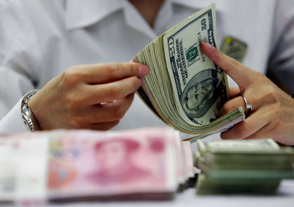 A bank teller counts the stack of Chinese yuan and US dollars at a bank in Shanghai, China.