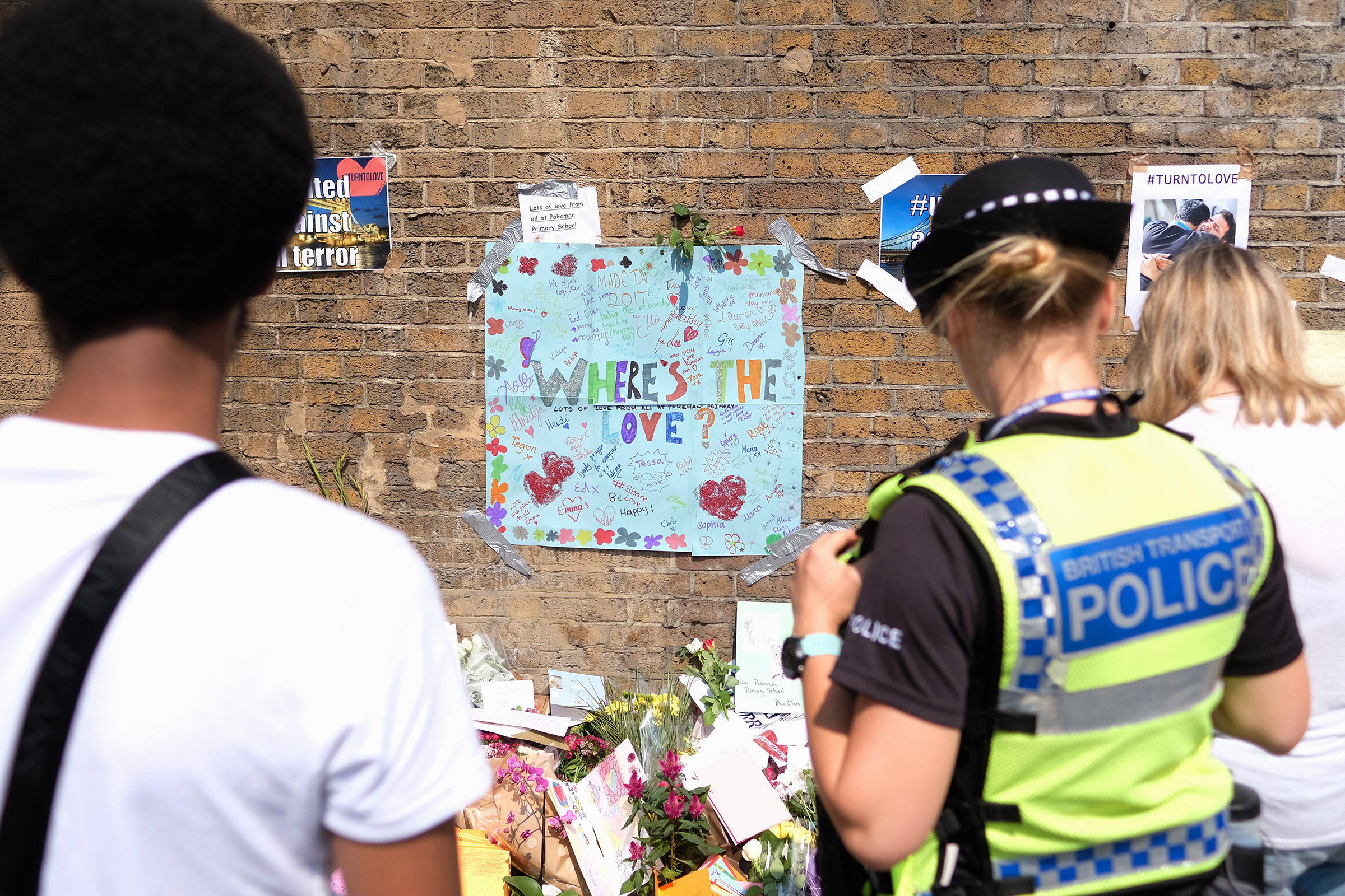 People stop to read some of the messages of support and love for the Muslim community near Finsbury Mosque on June 20, 2017 in London. A man was held on suspicion of attempted murder and alleged terror offenses after a group of Muslims were hit by a van in Finsbury Park.
