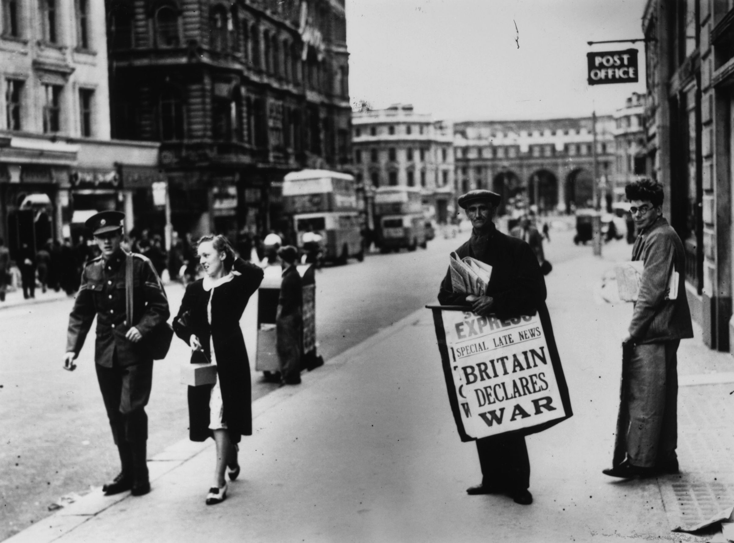 On Sept. 3, 1939, a newspaper seller carries a board  pronouncing the declaration of war between Britain and Germany, on the Strand, heading towards Admiralty Arch in London.