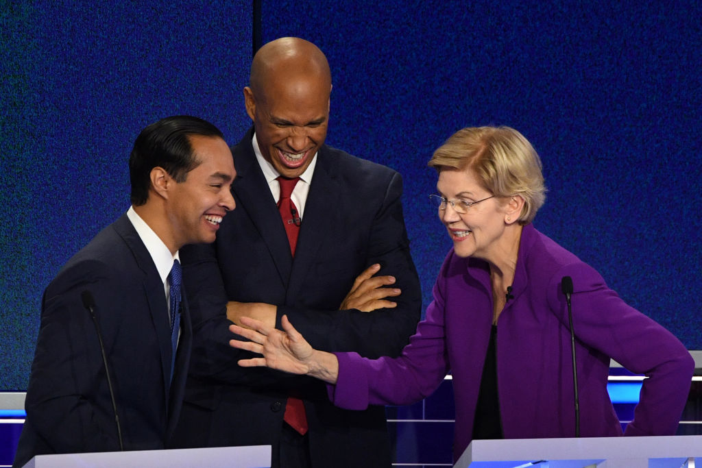Former US Secretary of Housing and Urban Development Julian Castro, US Senator from New Jersey Cory Booker and US Senator from Massachusetts Elizabeth Warren laugh during a break in the first Democratic primary debate of the 2020 presidential campaign season in Miami, Florida, June 26, 2019.