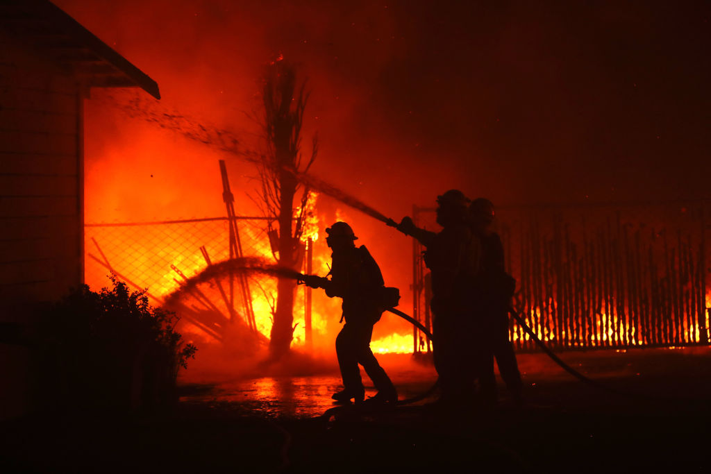 Firefighters battle the Kincade Fire as it burns a barn on Oct. 27, 2019 in Santa Rosa, California. Fueled by high winds, the Kincade Fire has burned over 66,000 acres and has prompted nearly 200,000 evacuations in Sonoma County and beyond.